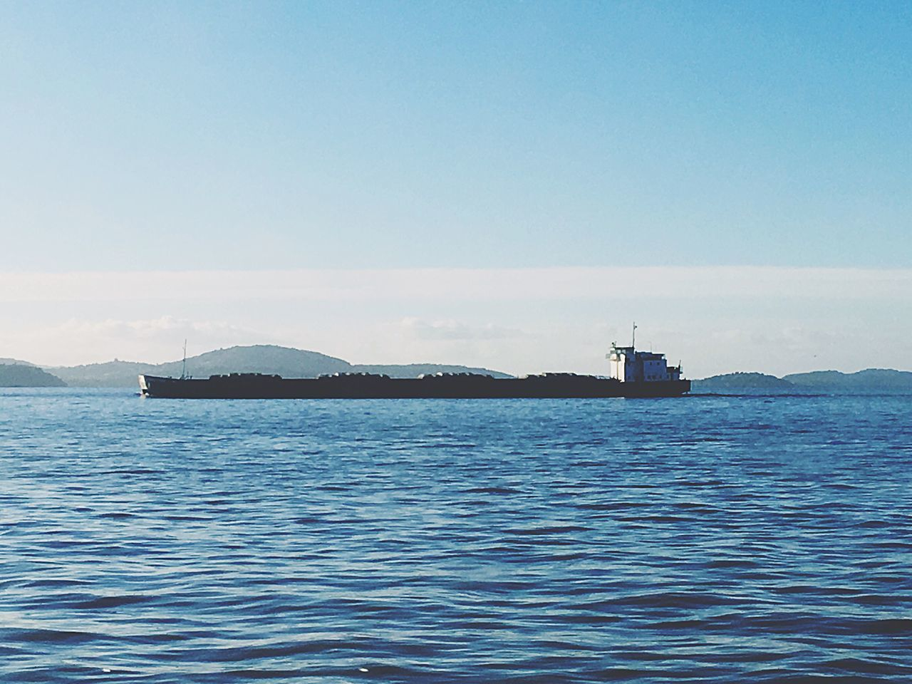 water, sea, nature, transportation, outdoors, tranquility, beauty in nature, nautical vessel, scenics, mountain, no people, mode of transport, day, waterfront, tranquil scene, copy space, blue, sky, rippled, mountain range, clear sky, sailing