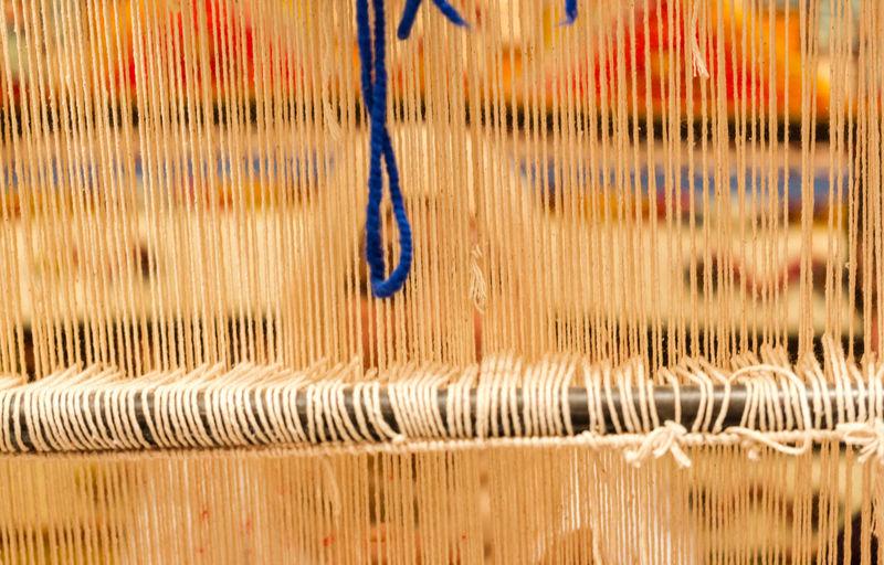 Berber woman weaving a traditional rug in medina souke in Marrakesh. Focus on strings Art Attraction Backgrounds Berber  Carpet Close-up Creation Design Face Handmade Hanging Hidden Indoors  Knitting Marrakech Morocco Ornament Persian Rural Scene Souks Strings Tedious Job Textured  Trade Vendor Weaving
