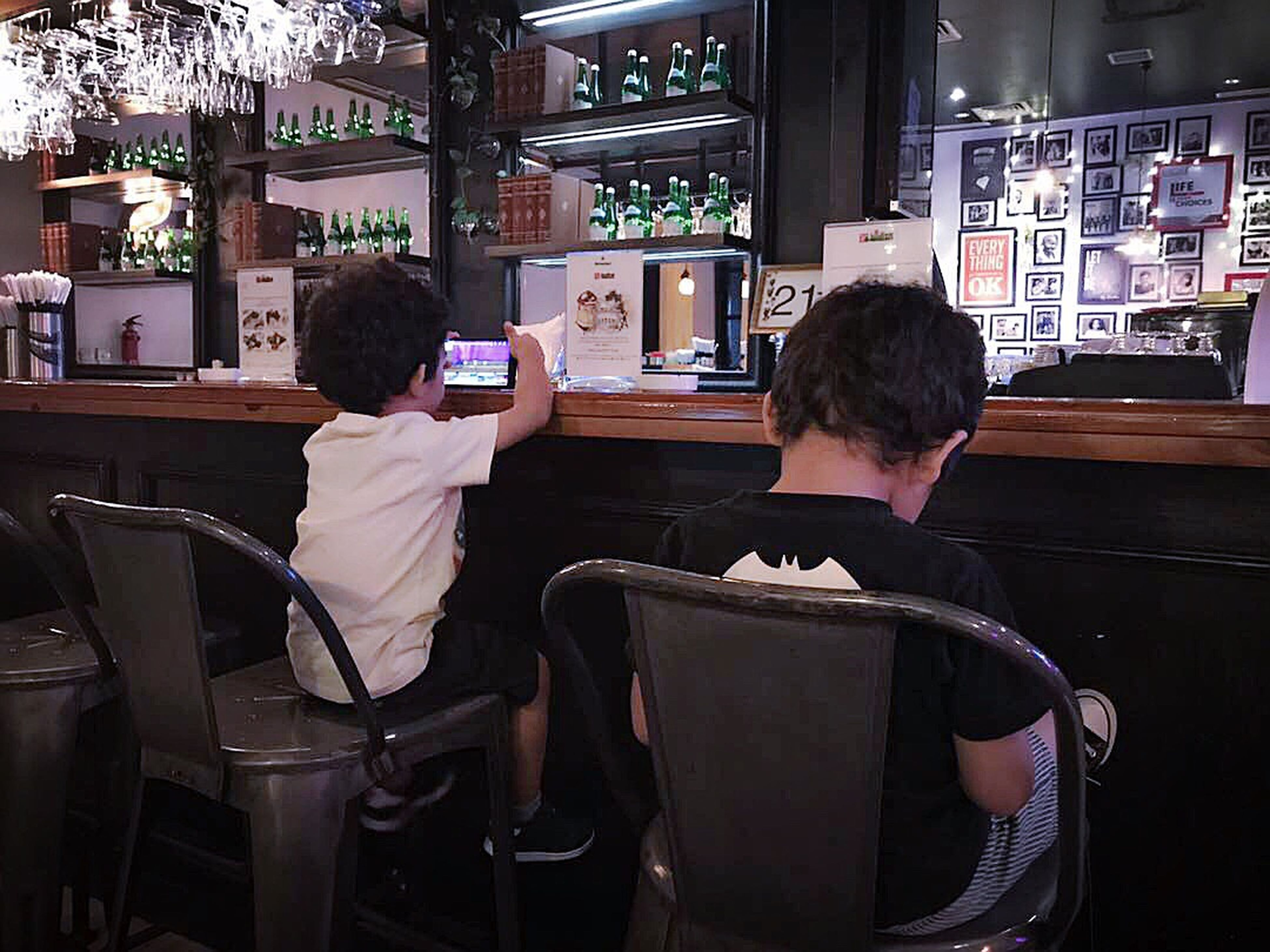 two people, restaurant, sitting, rear view, technology, cafe, leisure activity, lifestyles, chair, indoors, togetherness, real people, happiness, men, adult, people, vending machine, wireless technology, young adult, day, adults only, only men