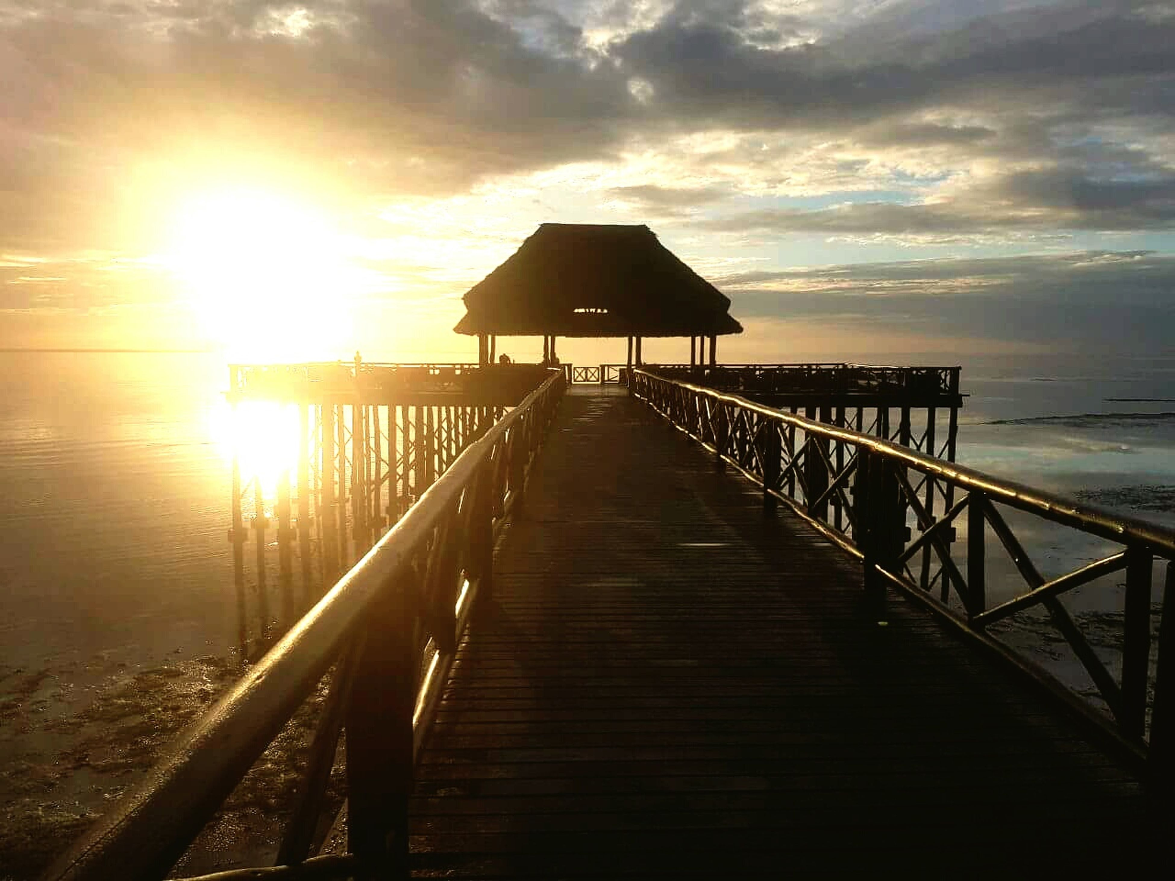 sunset, sunlight, nature, beauty in nature, sky, sea, tranquility, water, outdoors, idyllic, the way forward, railing, built structure, no people, scenics, tranquil scene, cloud - sky, architecture, horizon over water, day
