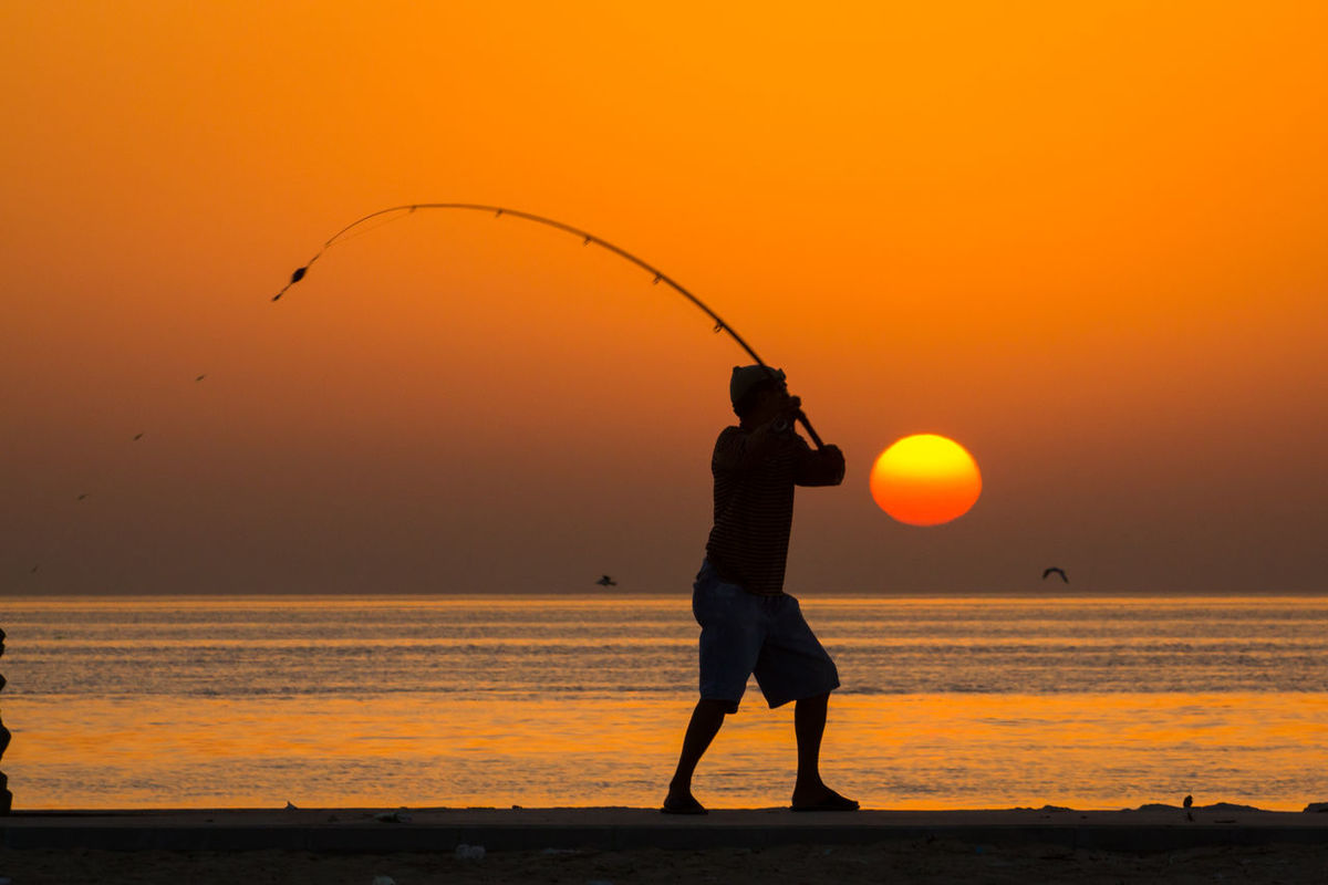 Adult Beach Beauty In Nature Clear Sky Day Full Length Holding Horizon Over Water Leisure Activity Lifestyles Men Nature One Man Only One Person Orange Color Outdoors Real People Scenics Sea Silhouette Skill  Sky Standing Sunset Water The Street Photographer - 2017 EyeEm Awards Mix Yourself A Good Time