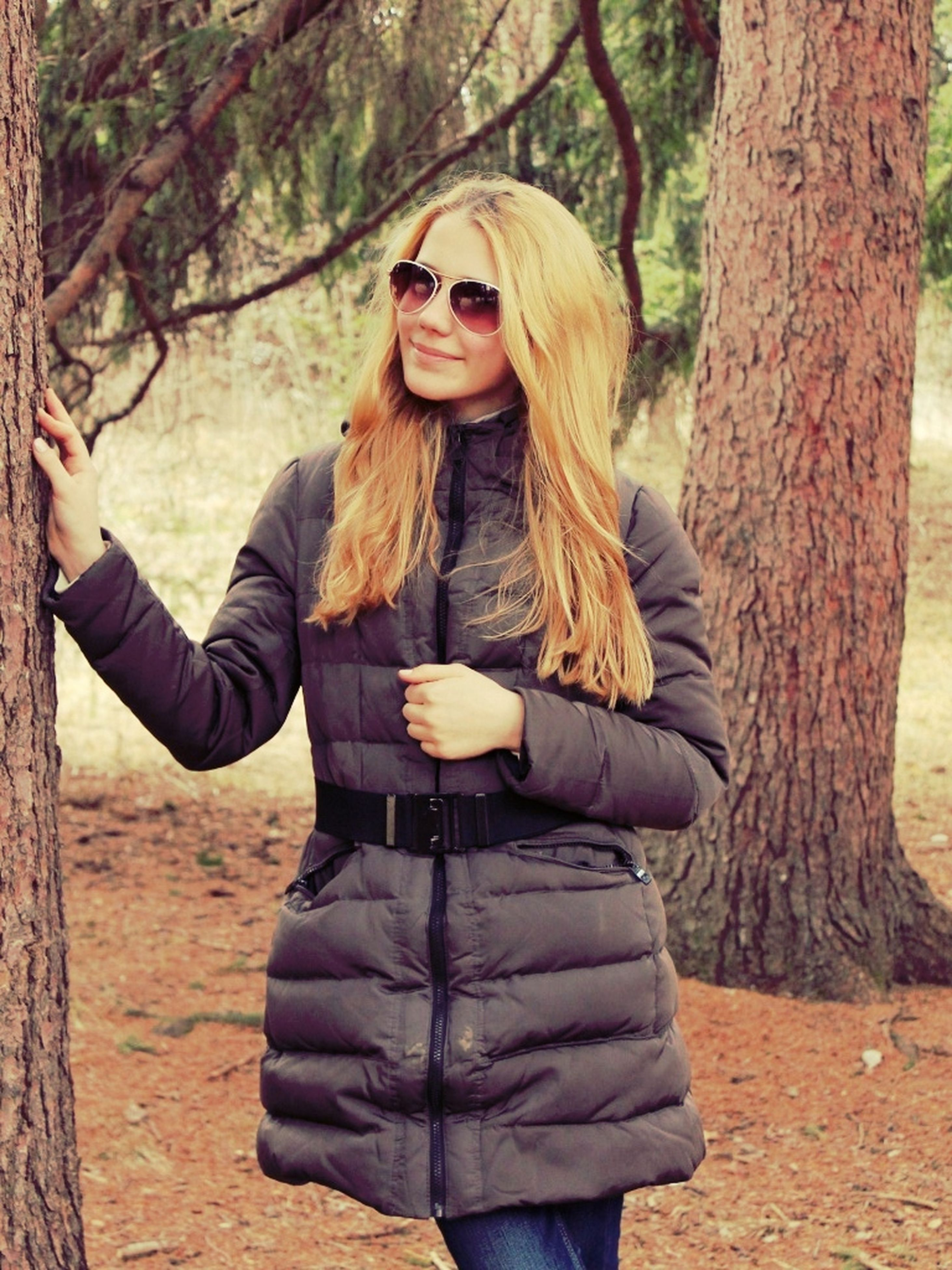 young adult, casual clothing, person, lifestyles, leisure activity, young women, standing, portrait, three quarter length, looking at camera, tree, front view, long hair, smiling, sunglasses, jacket, hands in pockets