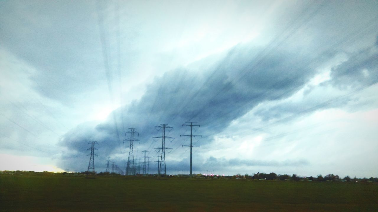 electricity pylon, cable, electricity, connection, power supply, power line, fuel and power generation, field, landscape, sky, cloud - sky, technology, day, electricity tower, no people, nature, tree, tranquility, outdoors, beauty in nature, scenics, low angle view, telephone line
