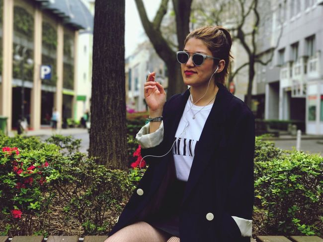 Sunglasses One Person Fashion Real People Outdoors Lifestyles Building Exterior Young Adult Holding Built Structure Focus On Foreground Portrait Young Women Leisure Activity Beautiful Woman Day Eyeglasses  Bad Habit Architecture Women