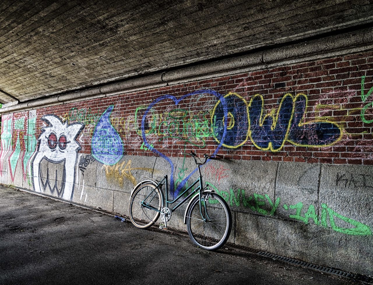 Saddle Stolen Architecture Art And Craft Bicycle Brick Wall Building Exterior Built Structure City Day Graffiti Left Multi Colored Neon Neon Color Neon Life Neon Lights No People Outdoors Spray Paint Stationary Street Art Transportation Wall - Building Feature