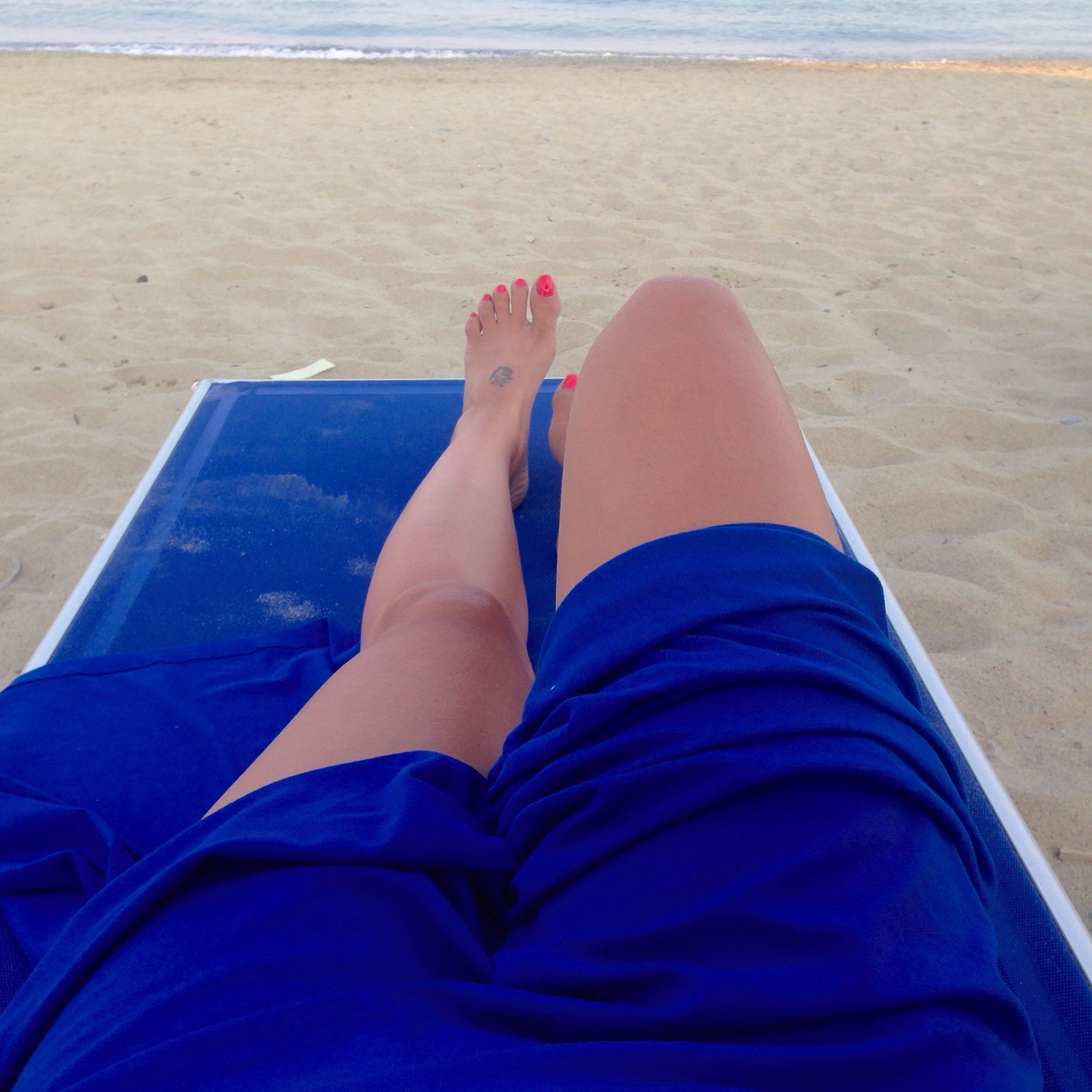 low section, person, personal perspective, relaxation, barefoot, lifestyles, human foot, leisure activity, sitting, blue, relaxing, legs crossed at ankle, resting, shoe, high angle view, sand