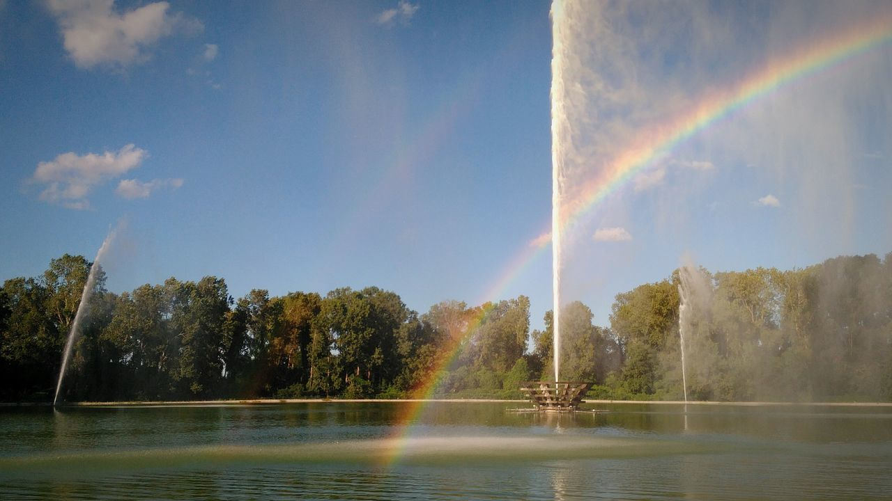 rainbow, water, double rainbow, scenics, nature, beauty in nature, idyllic, tree, tranquil scene, no people, sky, day, tranquility, outdoors, motion, waterfront, lake, spraying