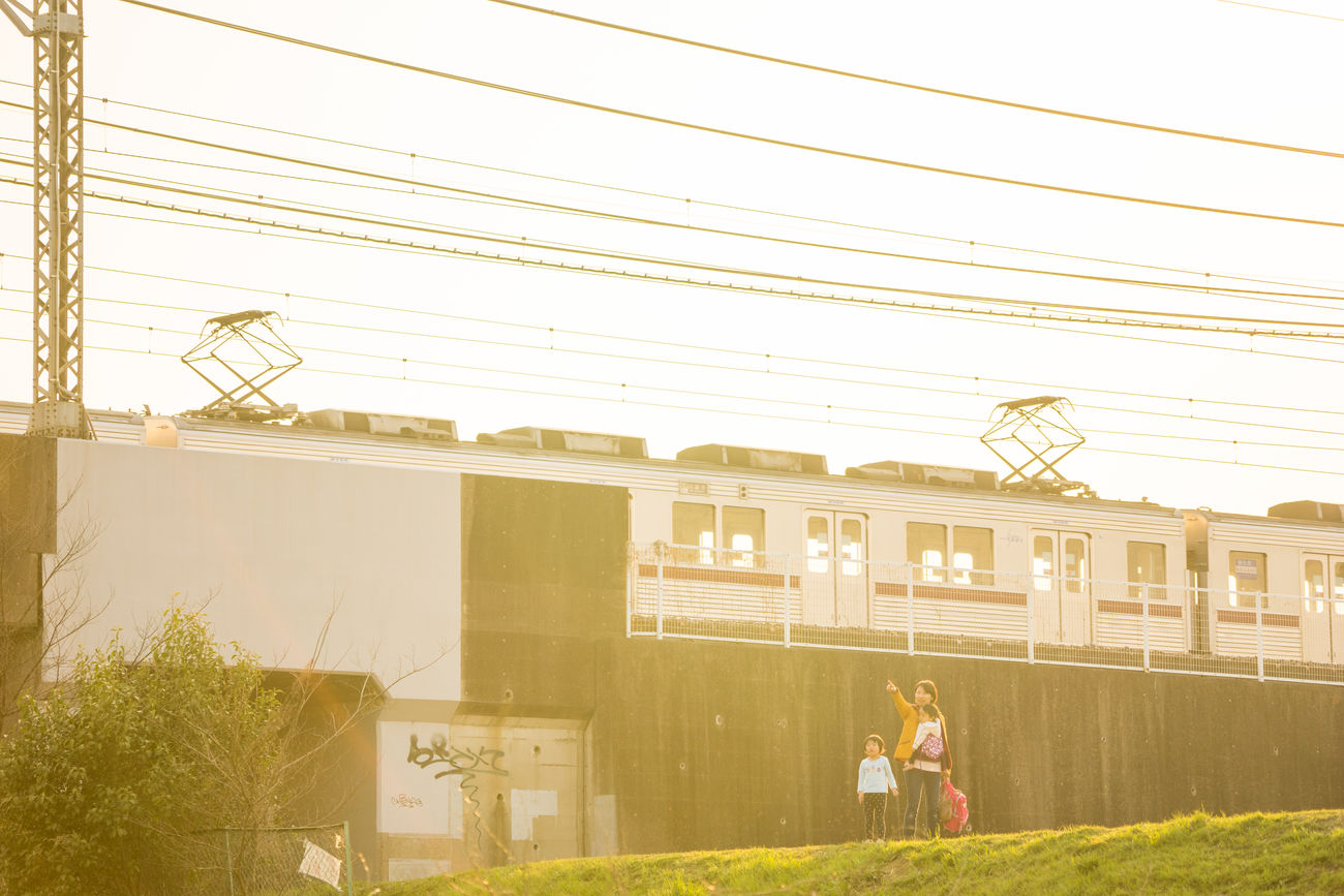 Evening and passing Train Architecture Building Exterior Built Structure Clear Sky Day Electricity Pylon Family Full Length Japanese  Lifestyles Men Modern Nature Outdoors People Real People Sky Standing Technology Train Transportation Warm Colors Women Young Adult Young Women