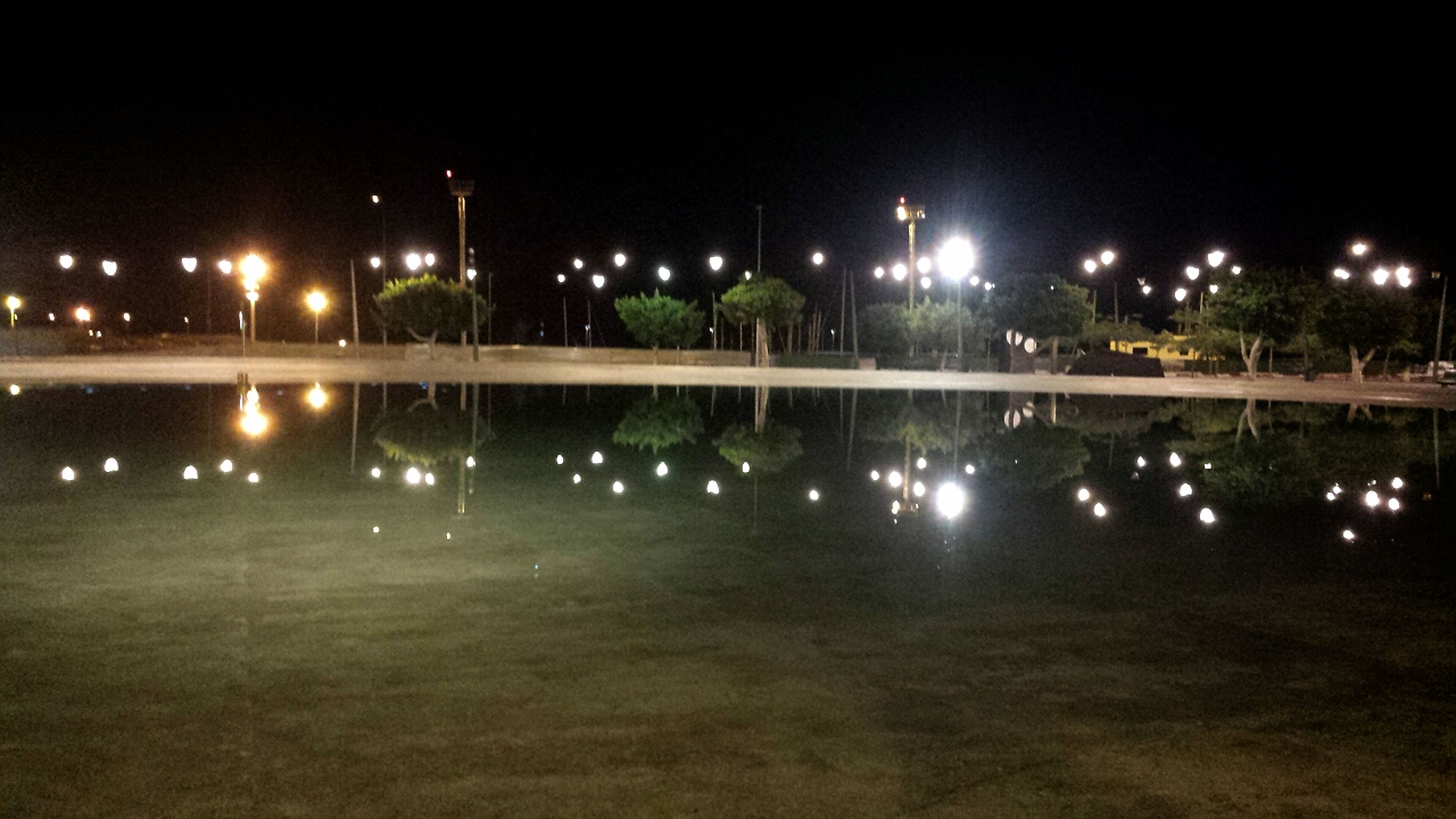 night, illuminated, street light, reflection, water, lighting equipment, built structure, architecture, building exterior, city, sky, fountain, light - natural phenomenon, outdoors, dark, clear sky, green color, park - man made space, waterfront, no people