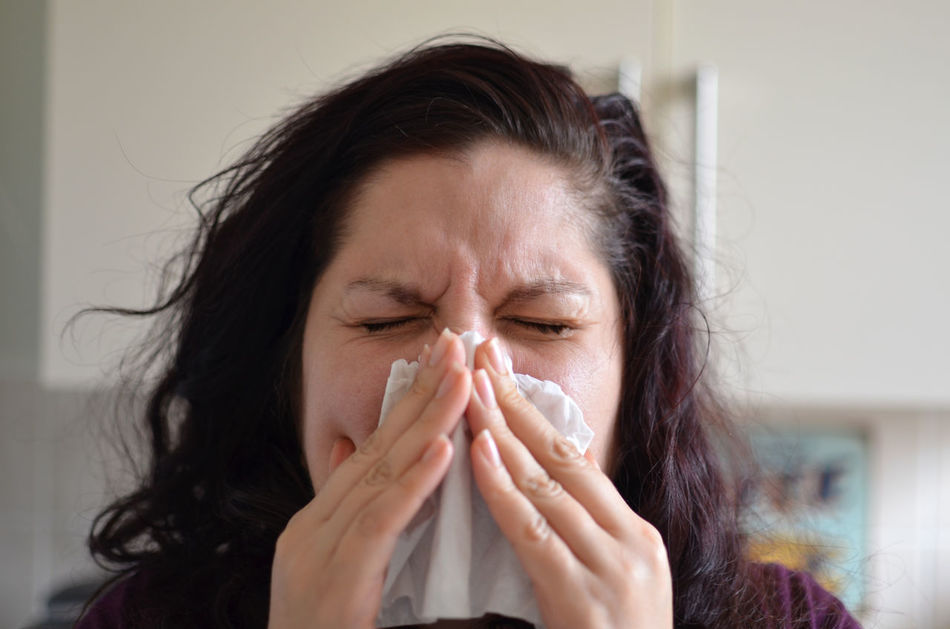 Woman blowing her nose hard into a tissue at home At Home Close-up Coughing Female Front View Headshot Health Home Human Face Human Hair Indoors  Long Hair Person Serious Sneeze Sneezing Sunglassess  Tissue Woman Young Adult Young Women