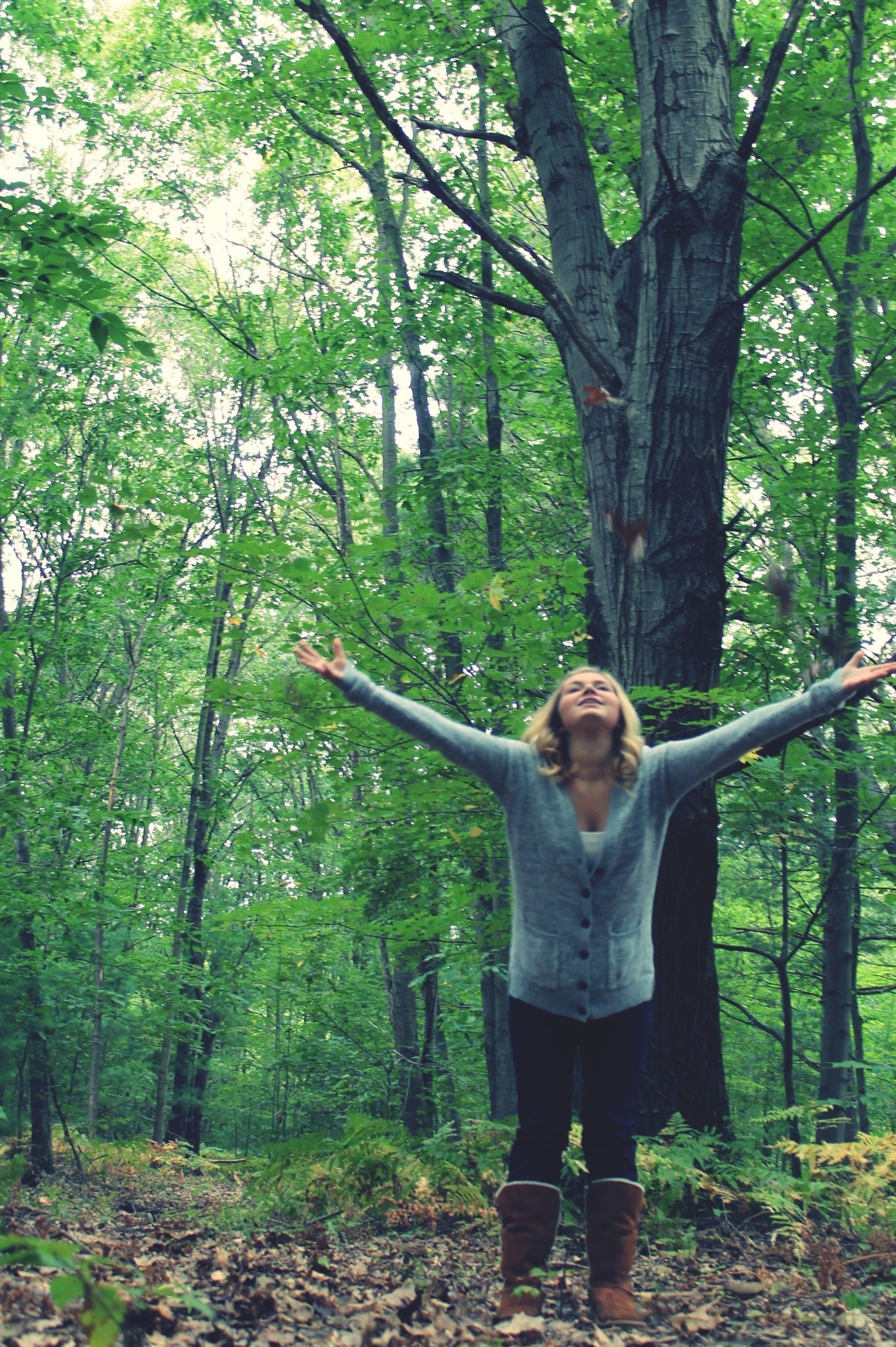 tree, young adult, casual clothing, forest, lifestyles, standing, person, leisure activity, young women, full length, tree trunk, growth, looking at camera, front view, portrait, woodland, three quarter length, nature