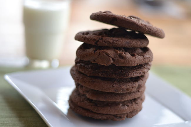 Stack of double chocolate chip cookies with glass of milk in the background. Baked Chocolate Close-up Comfort Food Cookies COOKIES! Dessert Dessert Double Chocolate Chip Cookies Focus On Foreground Food Food And Drink Glass Of Milk Indoors  Indulgence Milk And Cookies Ready-to-eat Snack Stack Still Life Sweet Food Table Temptation Treat Unhealthy Eating