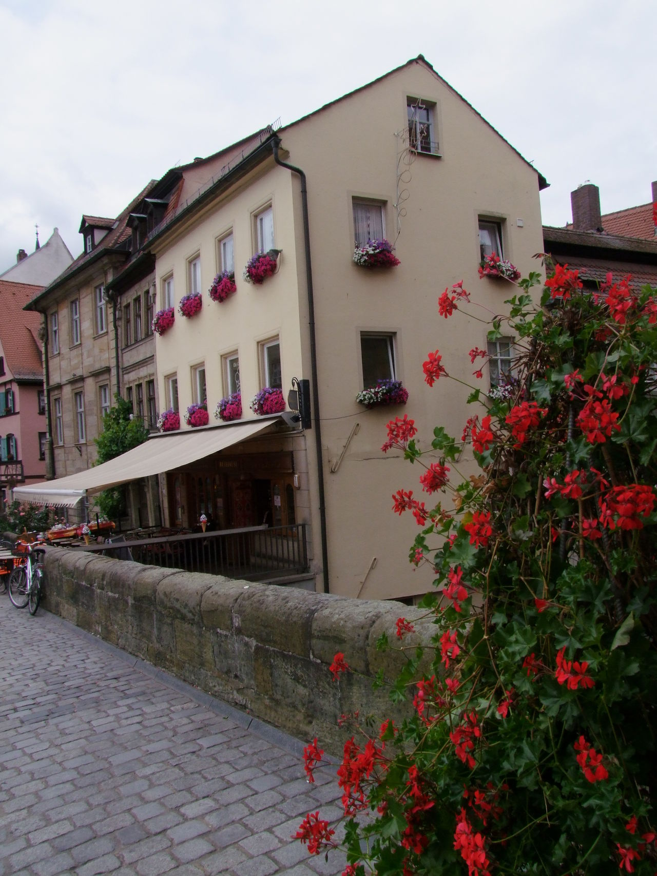 Bamburg Street Architecture Bamburgh Beauty In Nature Bridge Building Exterior Buildings Built Structure Cloudy Sky Cobblestones Composition Façade Flowers Full Frame Germany No People Outdoor Photography Plant Quaint  Quaint Perspective Red Residential Building Shop Toruism Tourist Destination Town