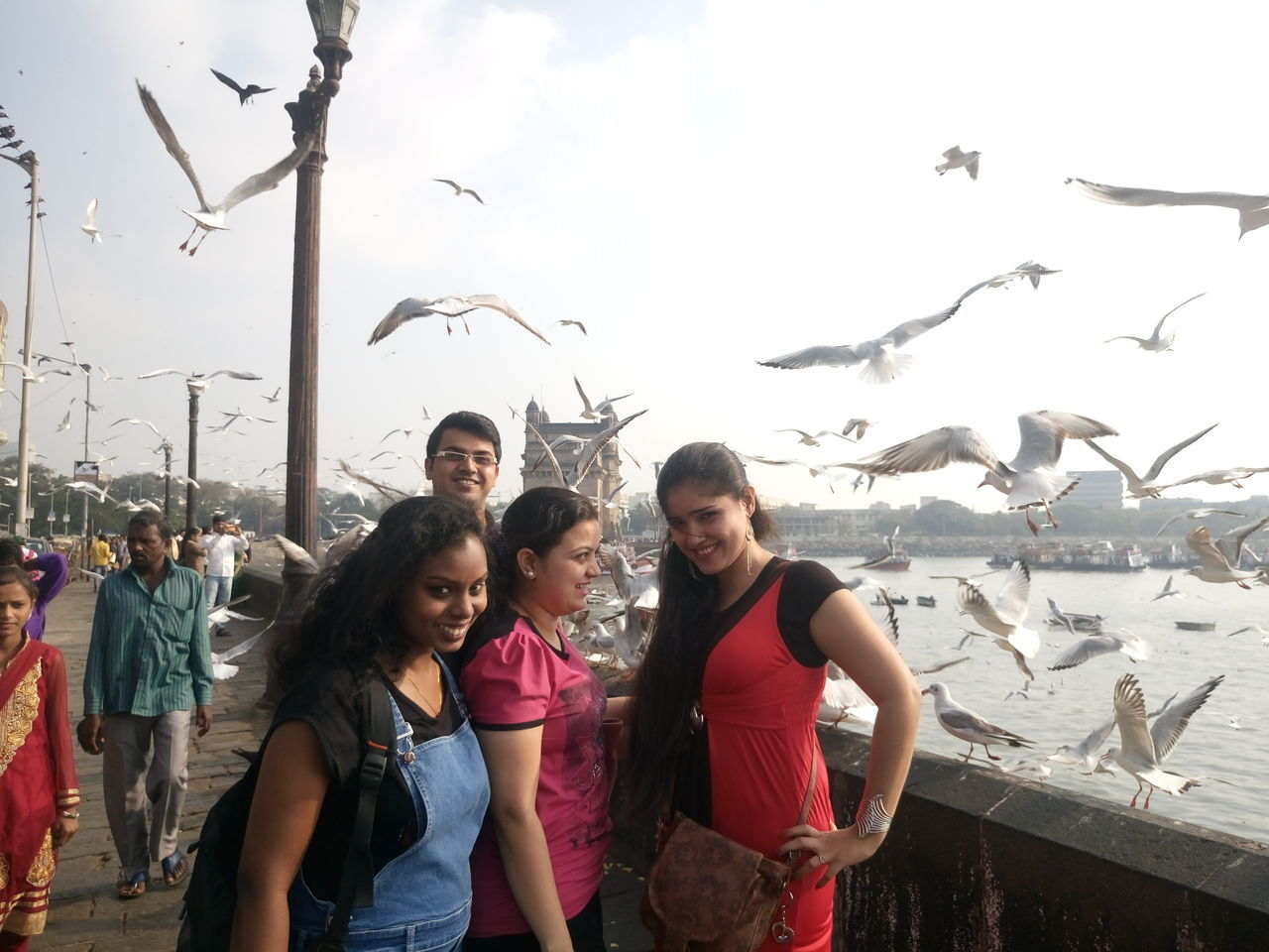 real people, leisure activity, lifestyles, casual clothing, togetherness, large group of animals, animal themes, standing, outdoors, day, portrait, animals in the wild, young women, young adult, looking at camera, bird, flying, boys, childhood, smiling, sky, nature