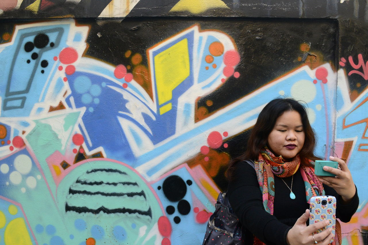 graffiti, one person, front view, standing, street art, real people, fun, leisure activity, lifestyles, multi colored, outdoors, building exterior, built structure, day, medium-length hair, architecture, only women, one woman only, young adult, adults only, people, adult