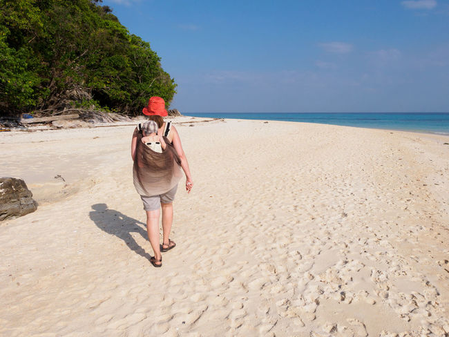 Woman with baby in carrier walking on a white sand beach on Koh Rok island, Thailand Adventure Baby Baby Carrier Beach Blue Sky Child Ko Rok Koh Rok Leisure Activity Lifestyles Nature Outdoors Parent People Real People Sand Sea Sunny Thailand Toddler  Travel Vacations Walking White Sand Woman