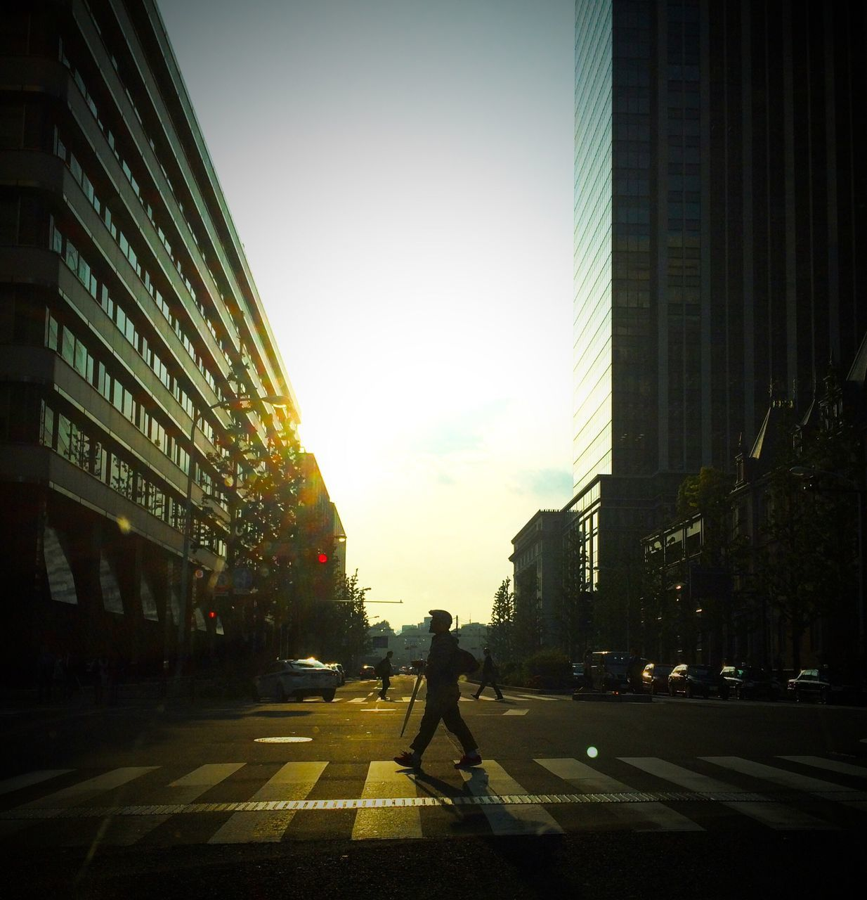Side view of a man crossing road along buildings