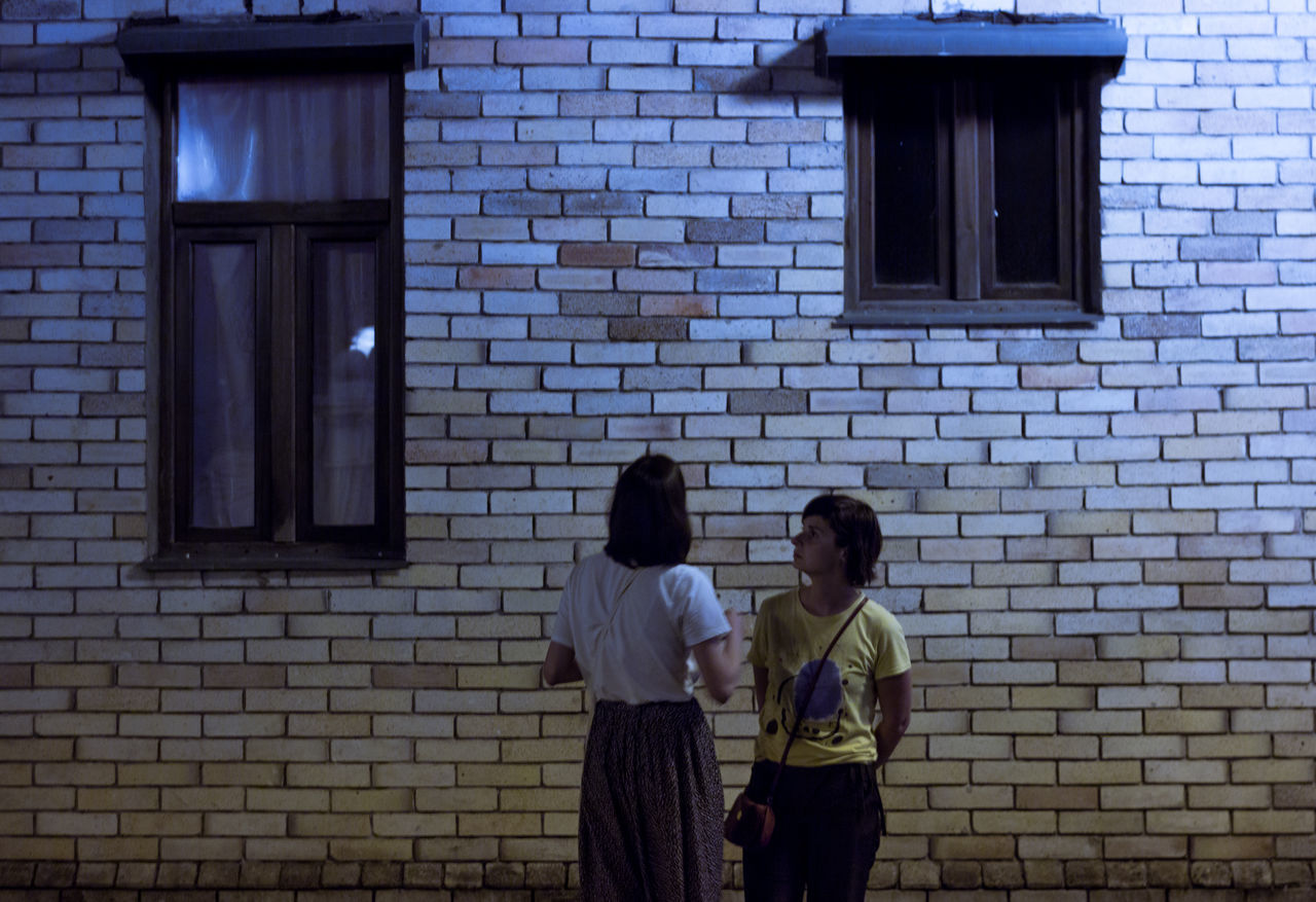 Adult Architecture Brick Wall Building Exterior Built Structure Day Friendship Lifestyles Men Outdoors People Real People Standing Togetherness Two People Window Women Young Adult Young Women