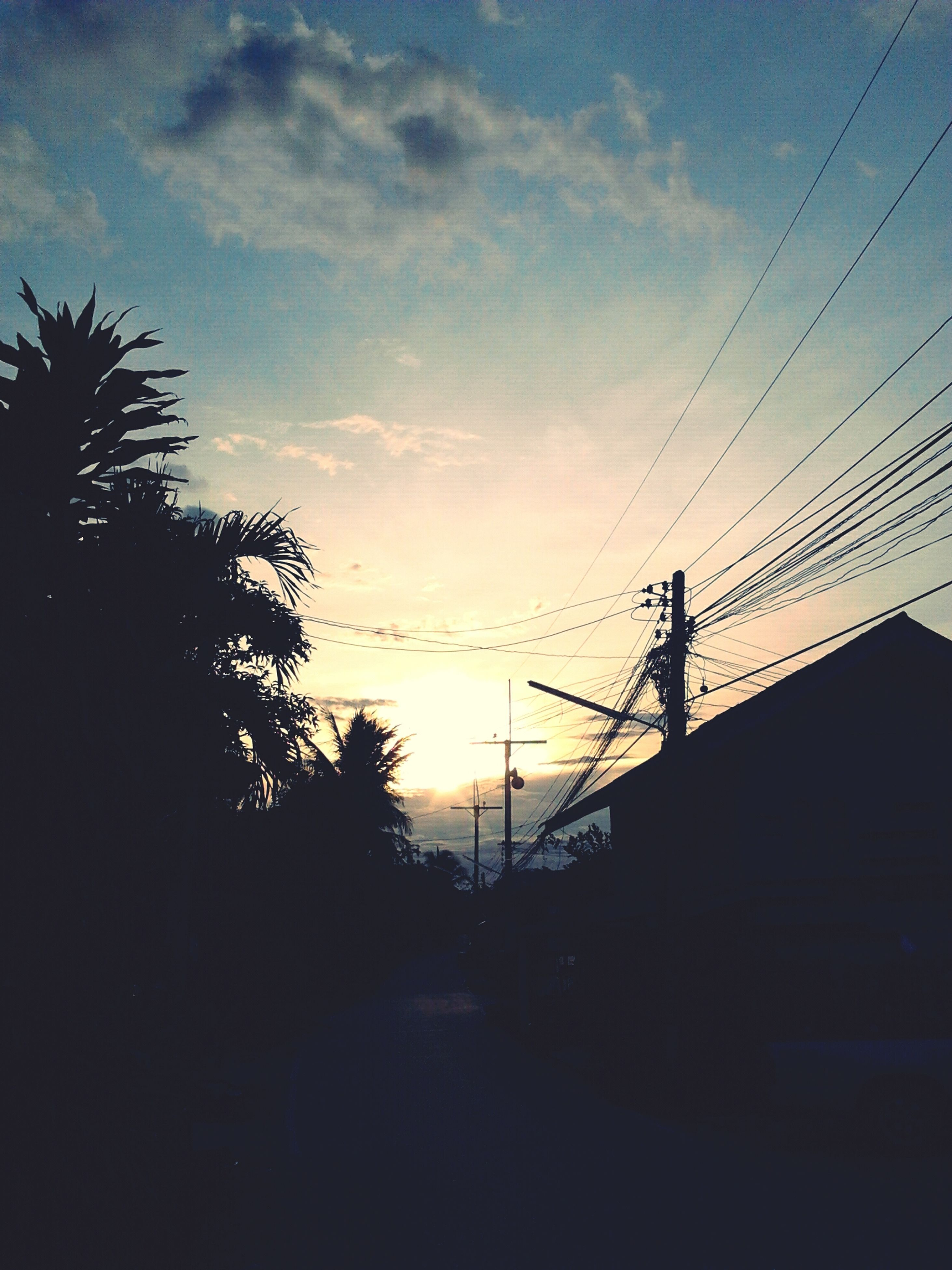 silhouette, electricity pylon, power line, sky, sunset, connection, tree, power supply, cable, electricity, cloud - sky, road, power cable, transportation, low angle view, cloud, built structure, nature, the way forward, dusk