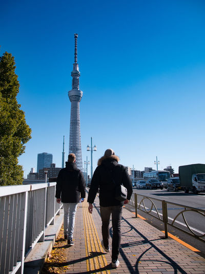 Architecture Blue Building Exterior Built Structure Casual Clothing City Clear Sky Couple - Relationship Day Full Length Leisure Activity Lifestyles Men Outdoors Real People Rear View Sky Standing Togetherness Tower Transportation Travel Travel Destinations Two People Women