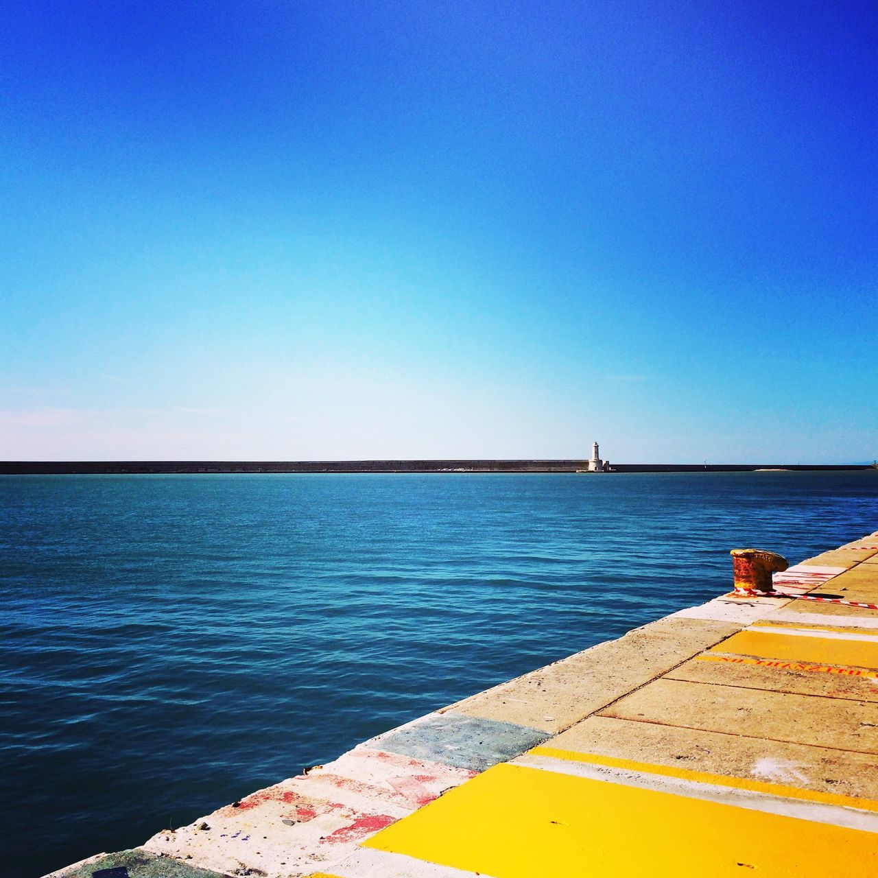 water, sea, blue, copy space, clear sky, nature, day, tranquility, scenics, outdoors, beauty in nature, no people, tranquil scene, horizon over water, sky, nautical vessel, retaining wall
