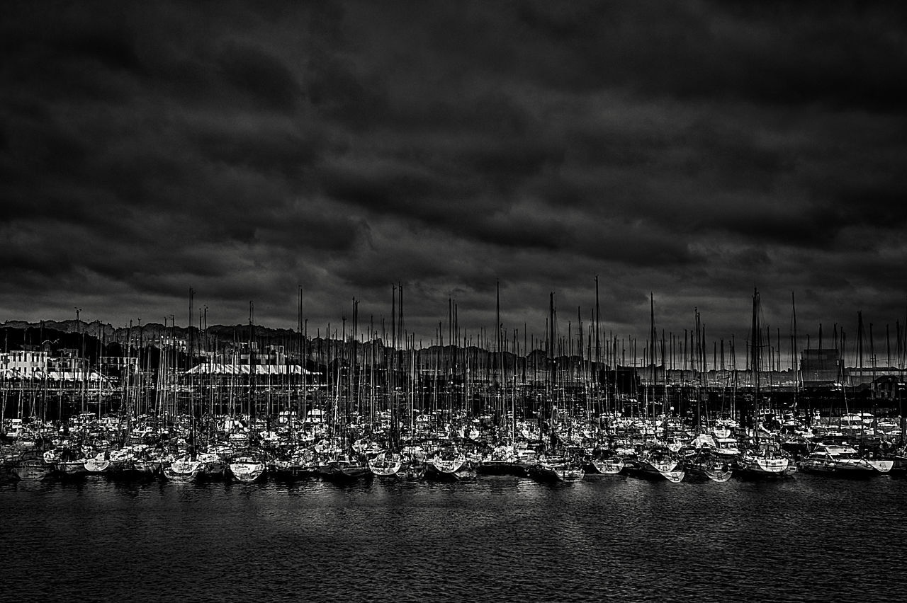 Nautical Vessels Moored At Harbor On Sea Against Cloudy Sky