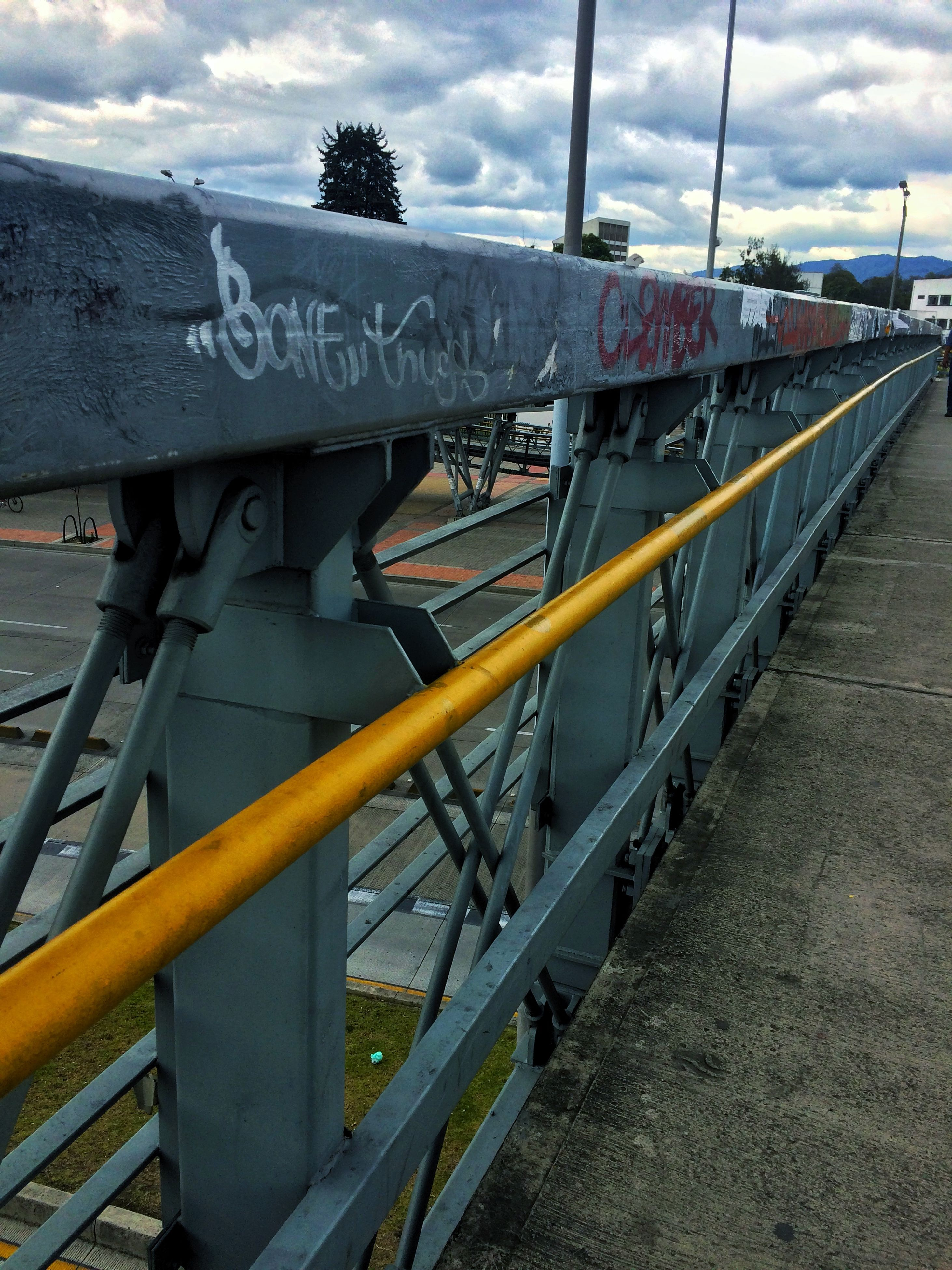 railing, transportation, metal, text, sky, bridge - man made structure, metallic, built structure, day, connection, no people, outdoors, western script, red, cloud - sky, sunlight, railroad track, communication, the way forward, architecture