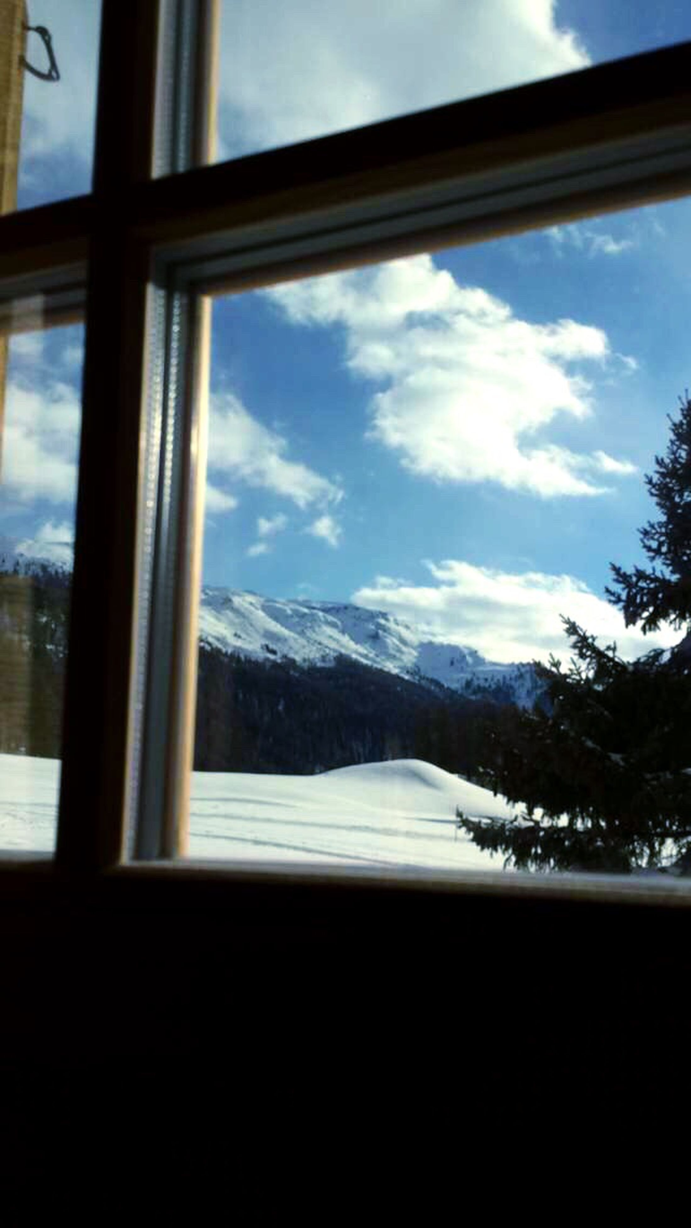 window, mountain, sky, transparent, glass - material, cloud - sky, indoors, cloud, mountain range, snow, winter, tree, landscape, cold temperature, scenics, day, nature, looking through window, tranquility, tranquil scene