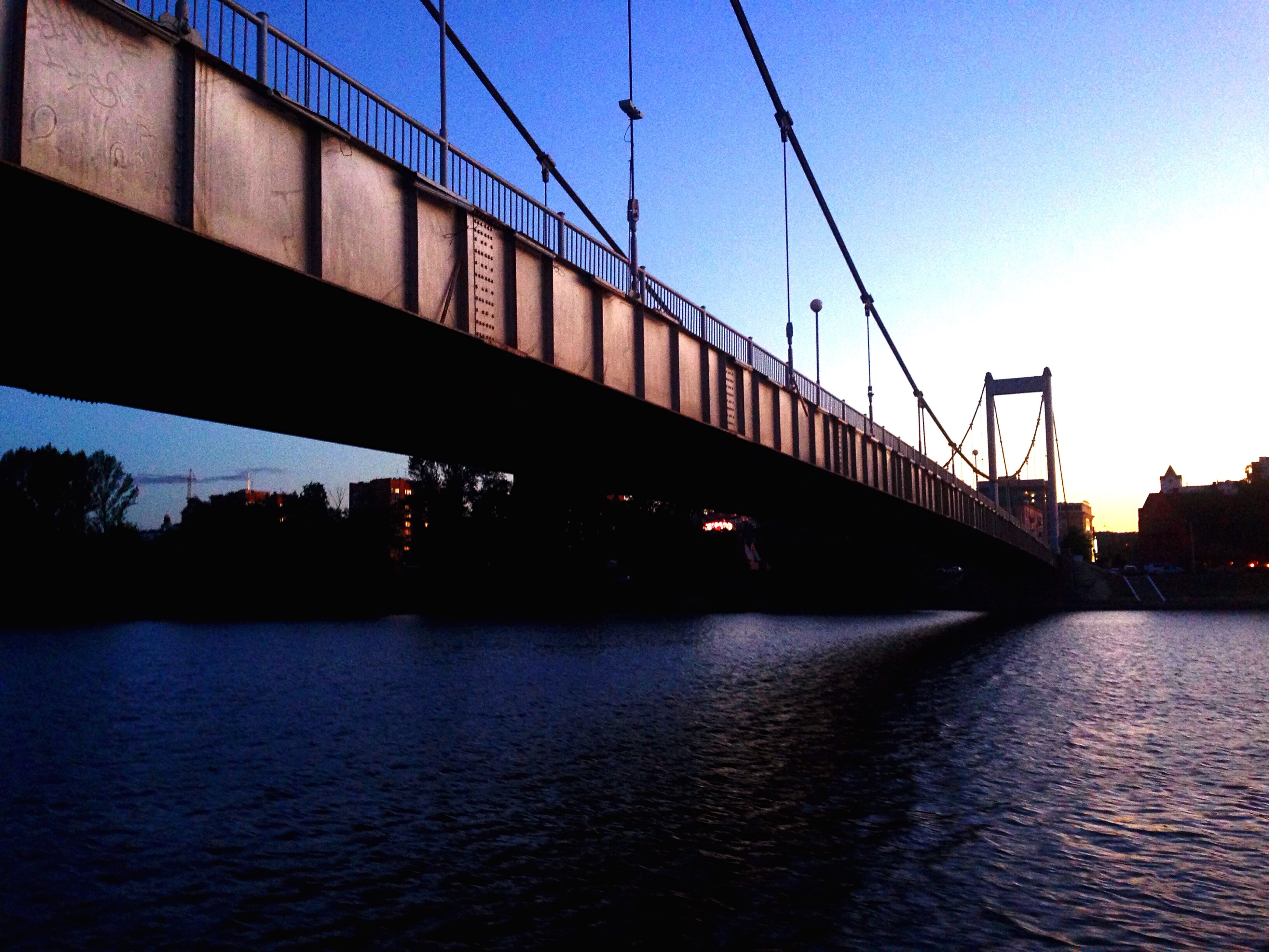 connection, architecture, built structure, bridge - man made structure, river, waterfront, water, bridge, clear sky, transportation, engineering, building exterior, sky, suspension bridge, low angle view, cable, reflection, city, rippled, silhouette