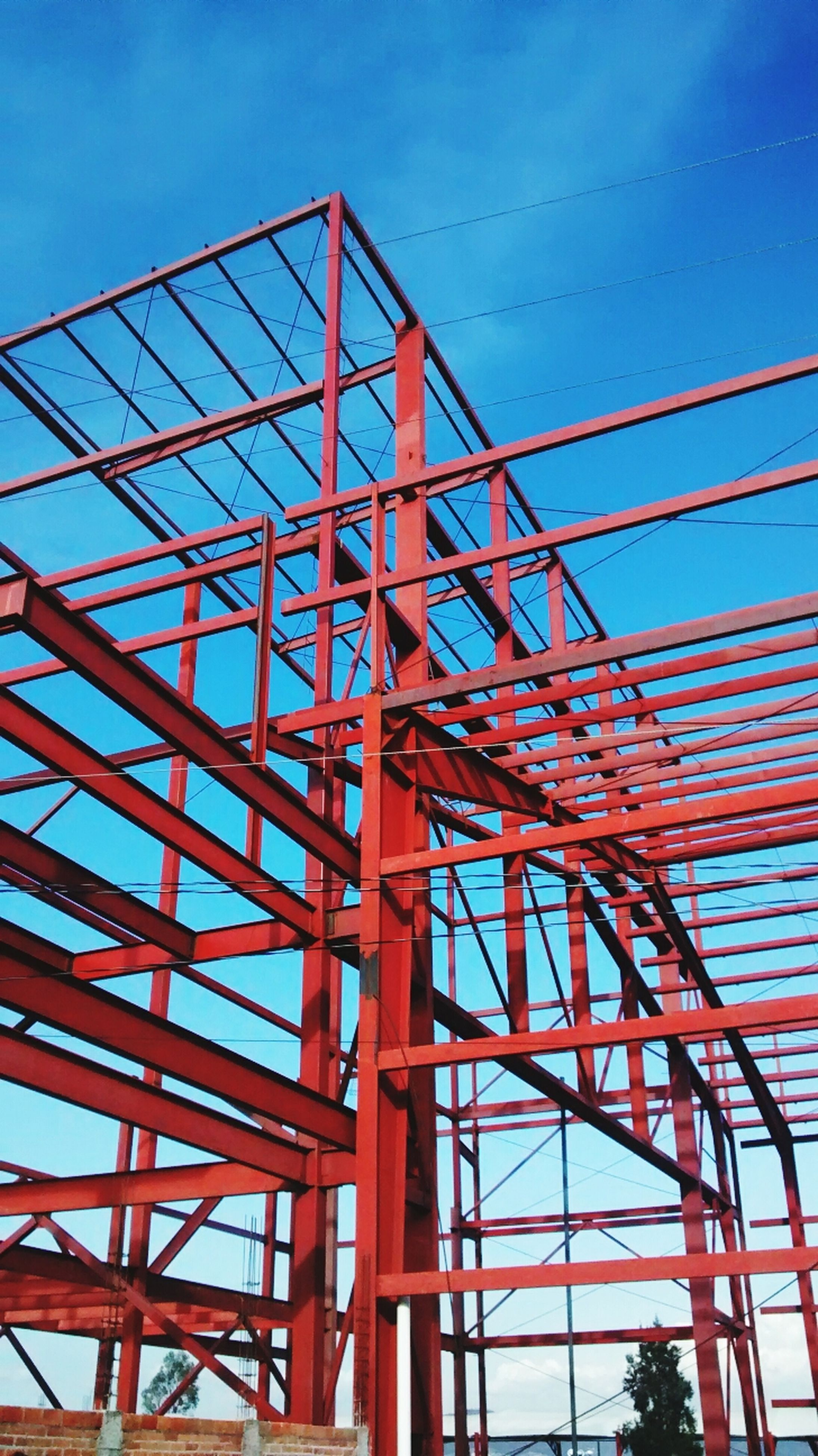 low angle view, built structure, blue, architecture, metal, connection, sky, clear sky, metallic, red, engineering, outdoors, no people, day, bridge - man made structure, sunlight, electricity pylon, structure, grid, transportation