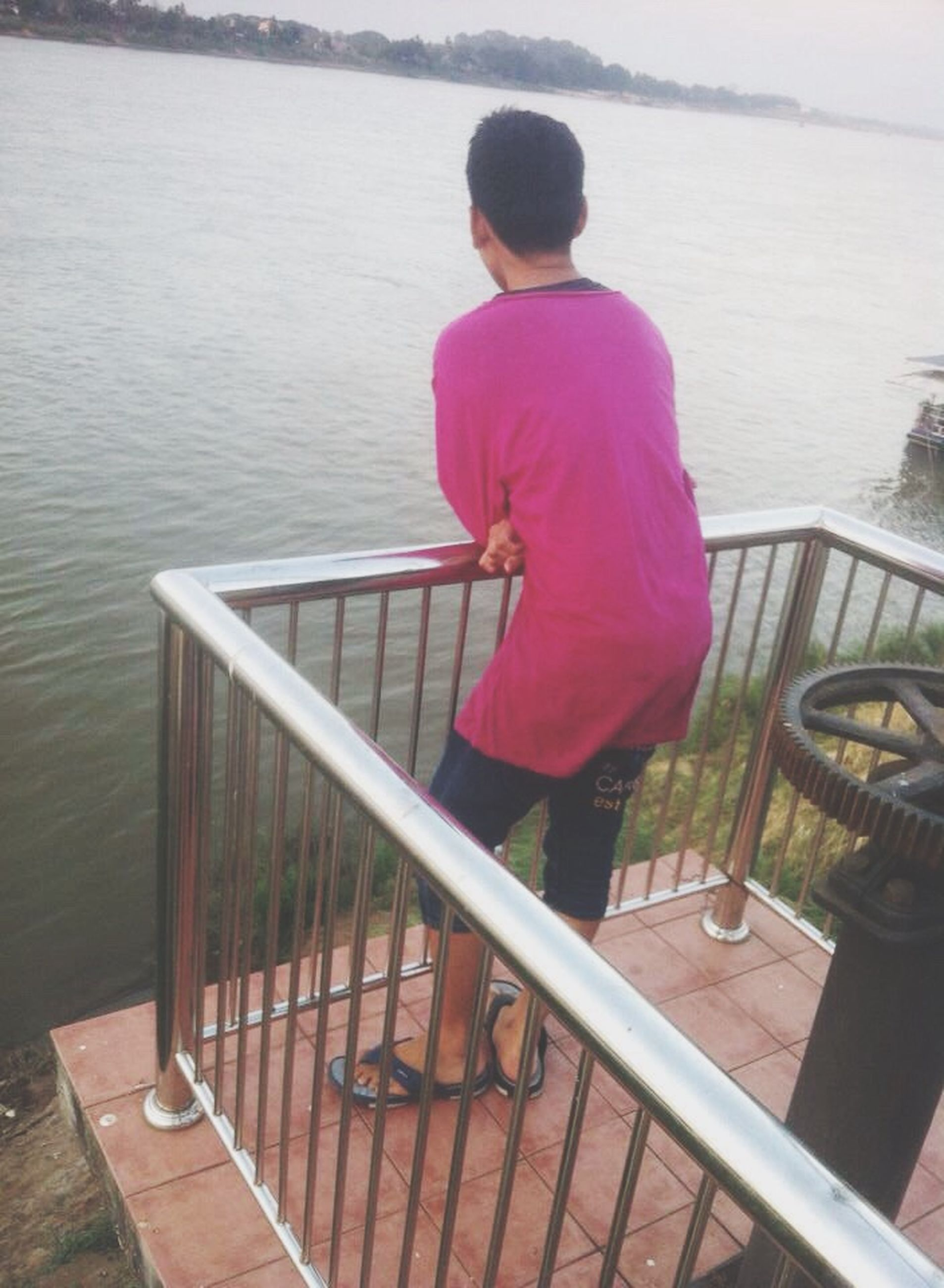 water, railing, full length, sitting, pier, lifestyles, leisure activity, casual clothing, rear view, lake, wood - material, relaxation, bench, standing, childhood, day, river, sea