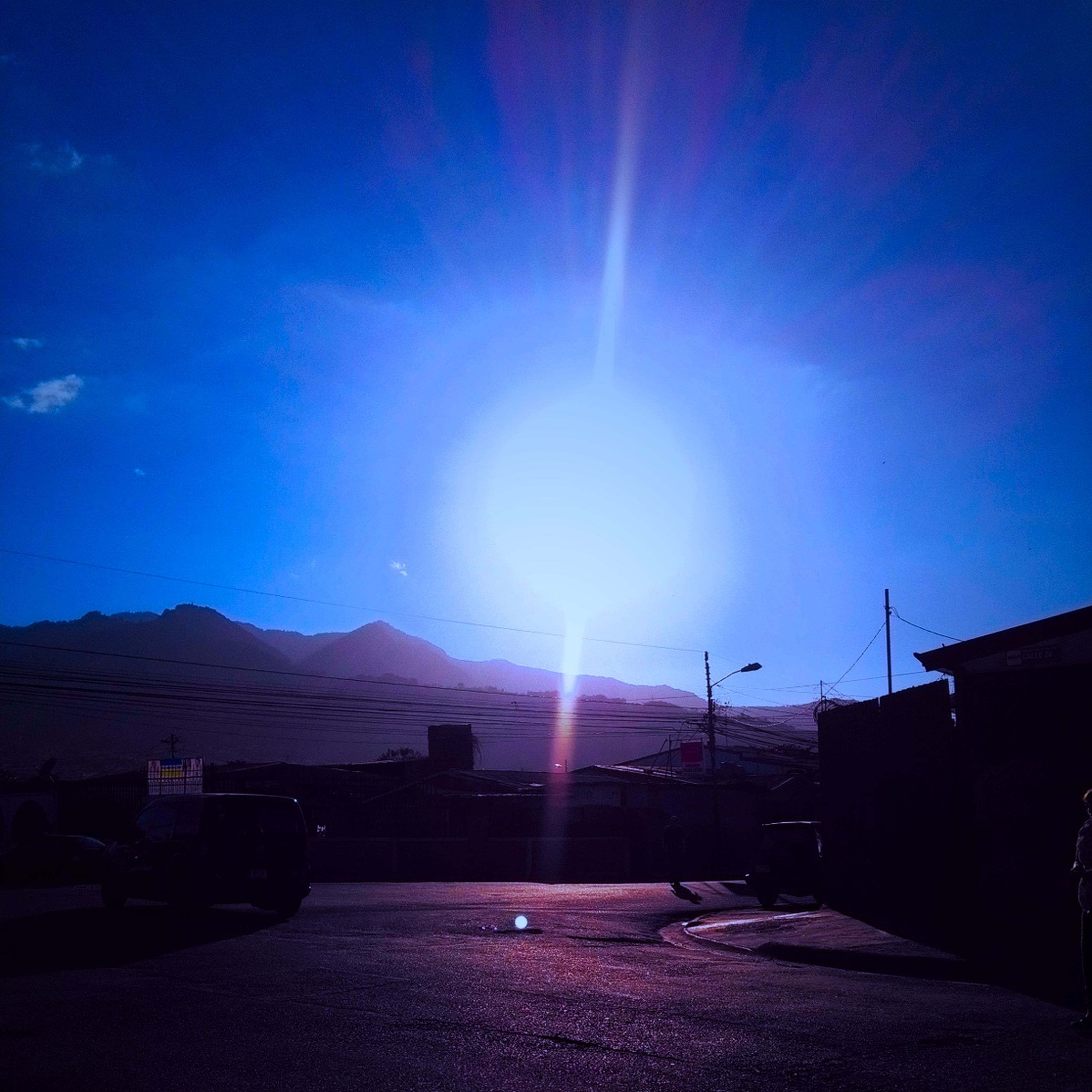 sun, sunbeam, sunlight, lens flare, building exterior, built structure, architecture, blue, sky, house, sunny, bright, clear sky, nature, outdoors, silhouette, car, sunset, road, mountain