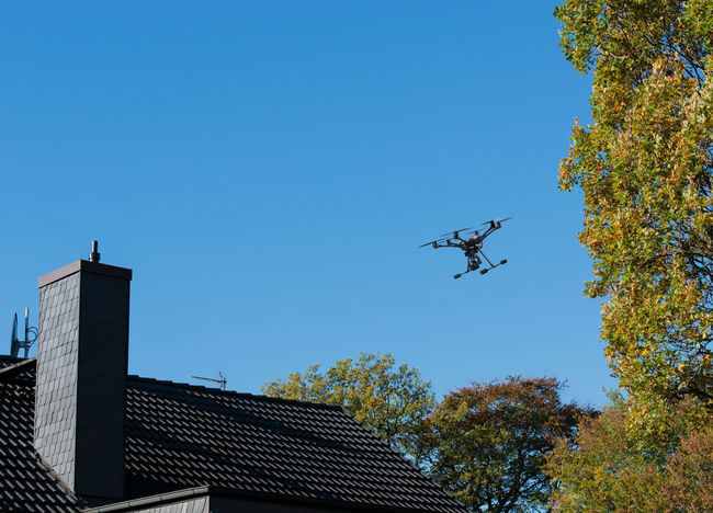 Drone flies illicitly over a residential area Drone  Hexacopter Landing Noise Octocopter Quadrocopter Aircraft Aircraft Noise Aviation Building Buoyancy Concept Departure Disturbing Flying House Illicit Lawsuit License No-fly Permission Propeller Residential Area Rotors TakeOff