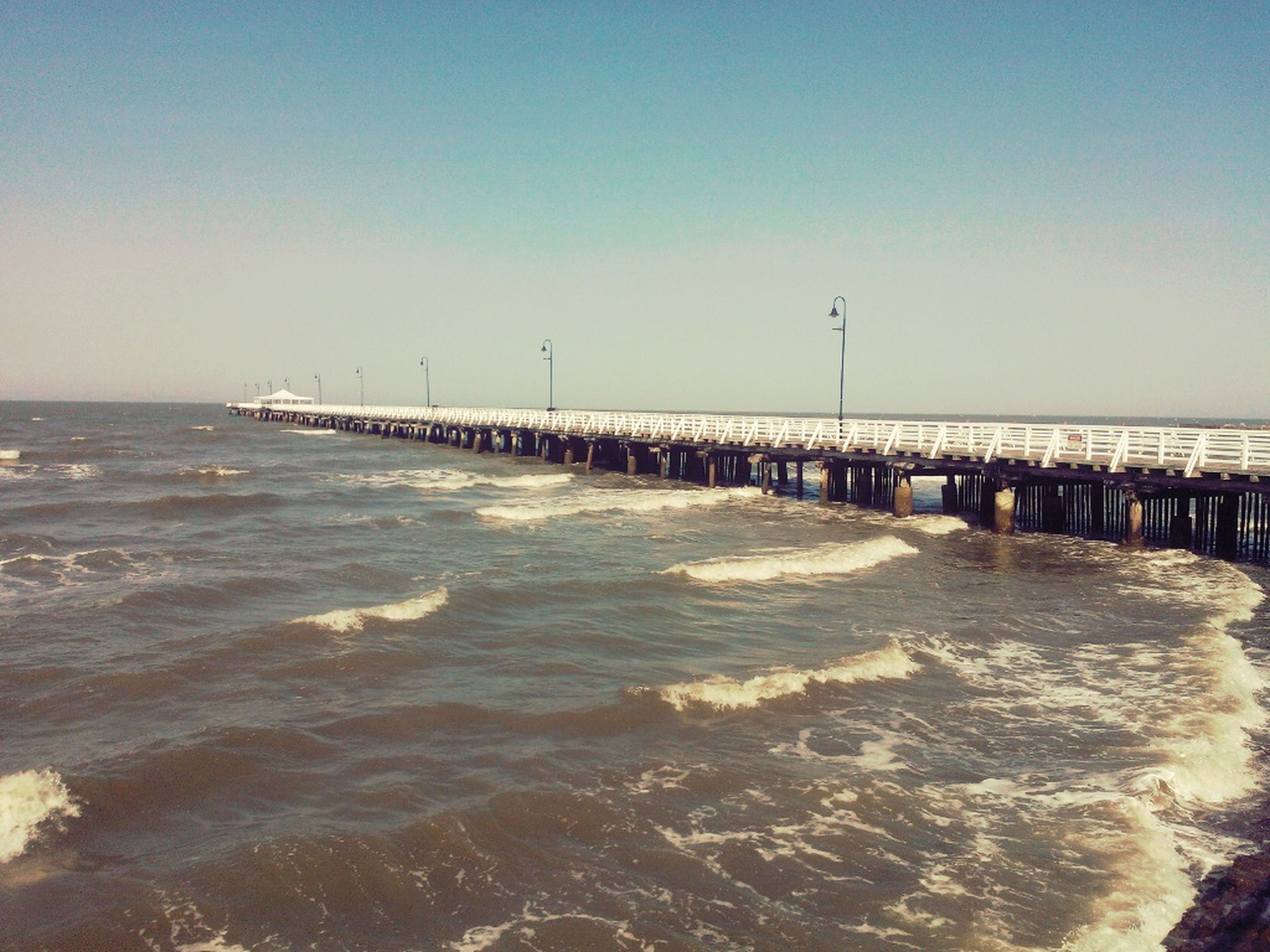 sea, water, clear sky, horizon over water, beach, copy space, scenics, tranquil scene, tranquility, pier, wave, beauty in nature, shore, nature, built structure, surf, blue, idyllic, sand, incidental people
