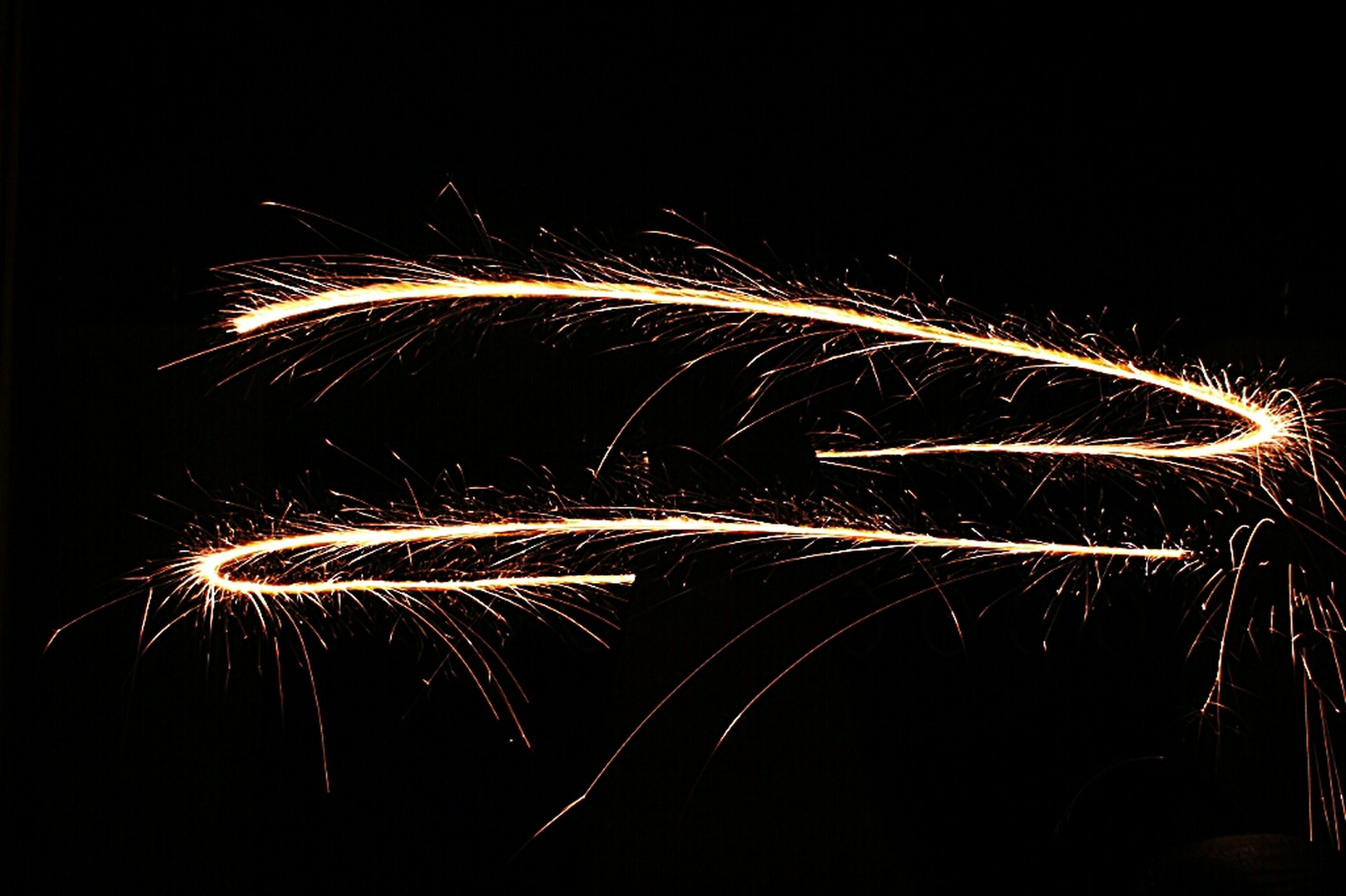 night, long exposure, illuminated, motion, celebration, firework display, light trail, exploding, blurred motion, arts culture and entertainment, firework - man made object, glowing, event, multi colored, sparks, firework, abstract, copy space, speed, light painting