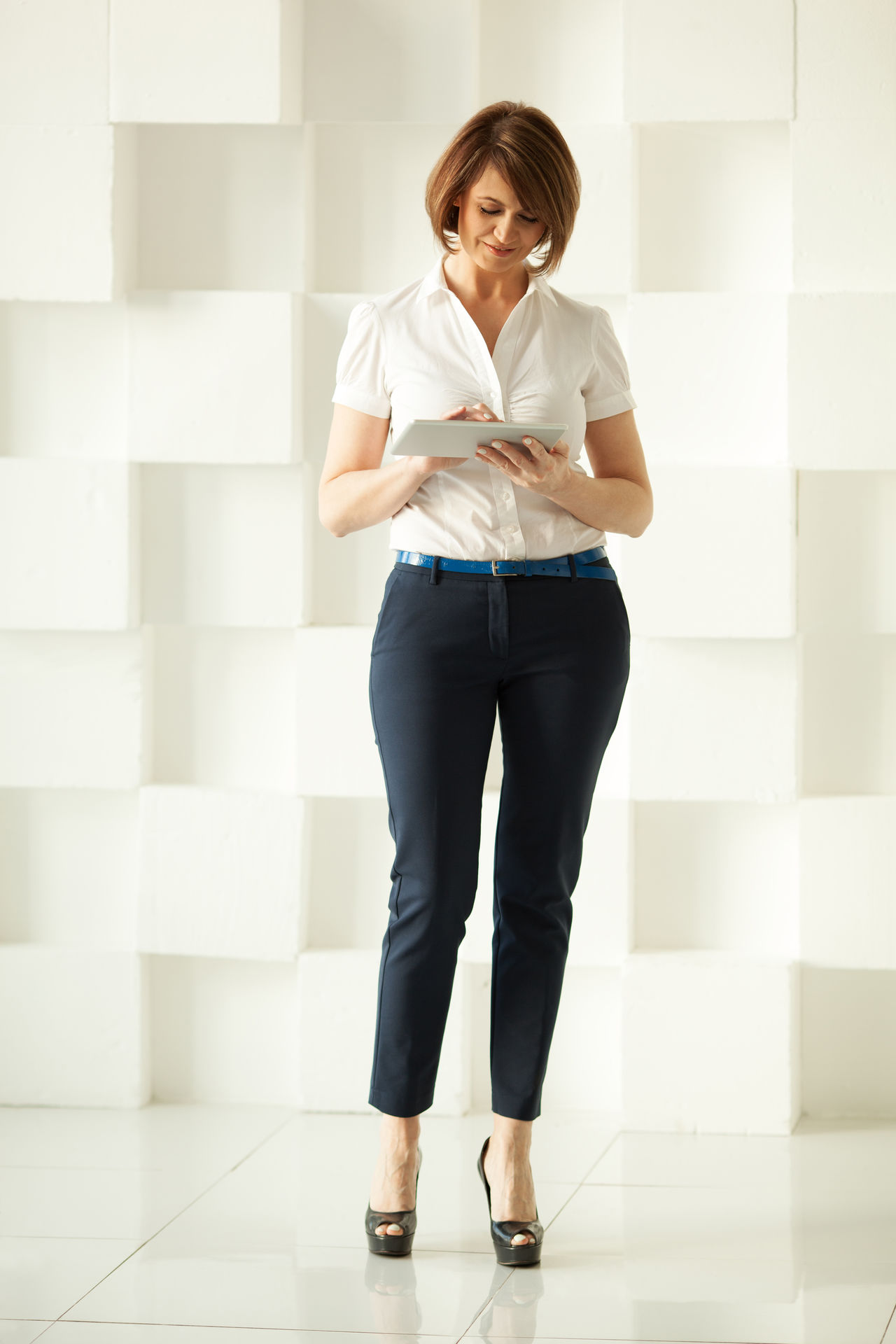 Smiling businesswoman standing against white wall while looking at tablet in her hand Business Businesswoman Caucasian Corporate Elegant Elegante Facial Expressions Gadget Hands Holding Light Hair Manager Office Short Hair Smiling Sunlight Tablet Vertical White Young