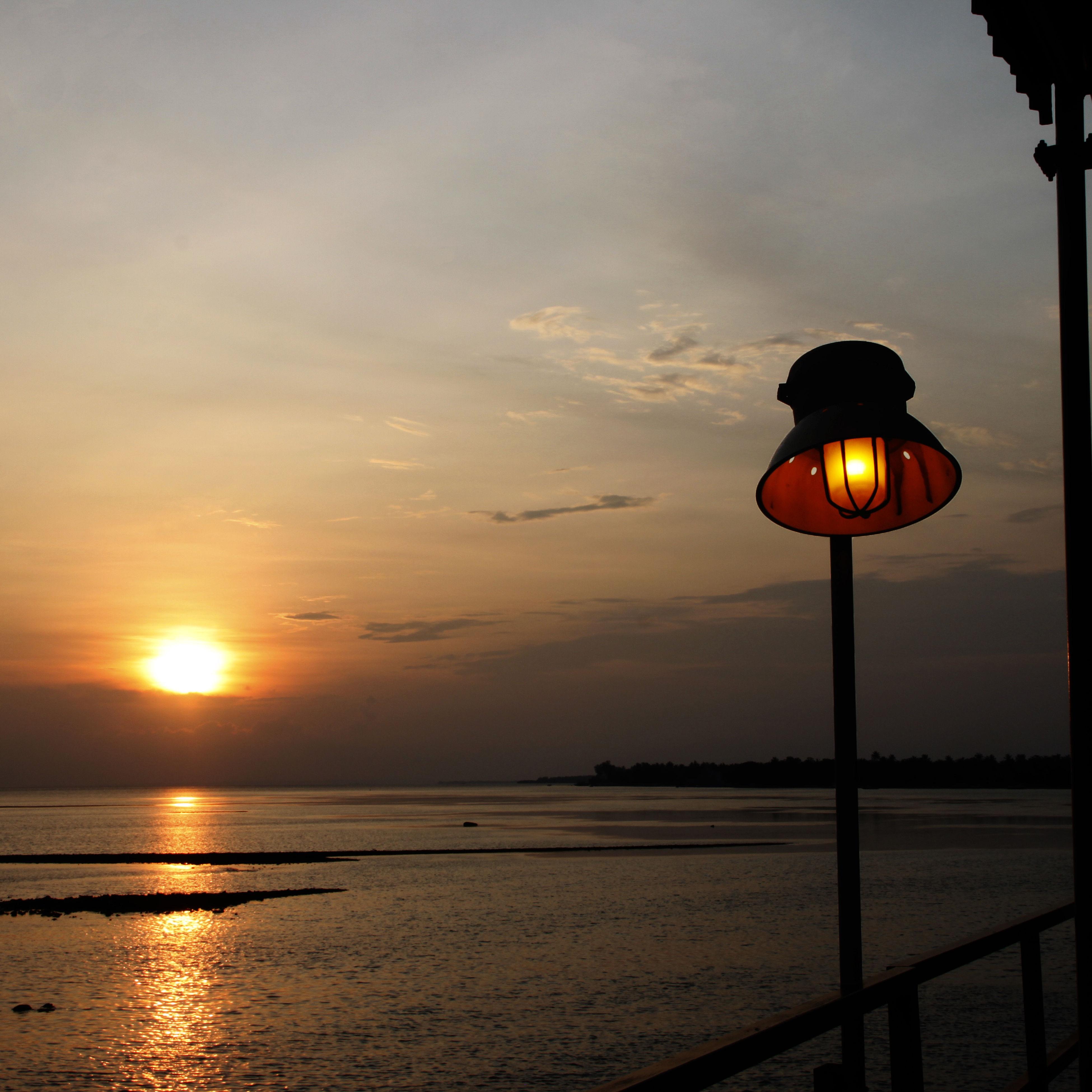 sunset, water, sky, sea, scenics, street light, tranquility, tranquil scene, lighting equipment, beauty in nature, sun, orange color, illuminated, nature, silhouette, idyllic, cloud - sky, reflection, horizon over water, beach