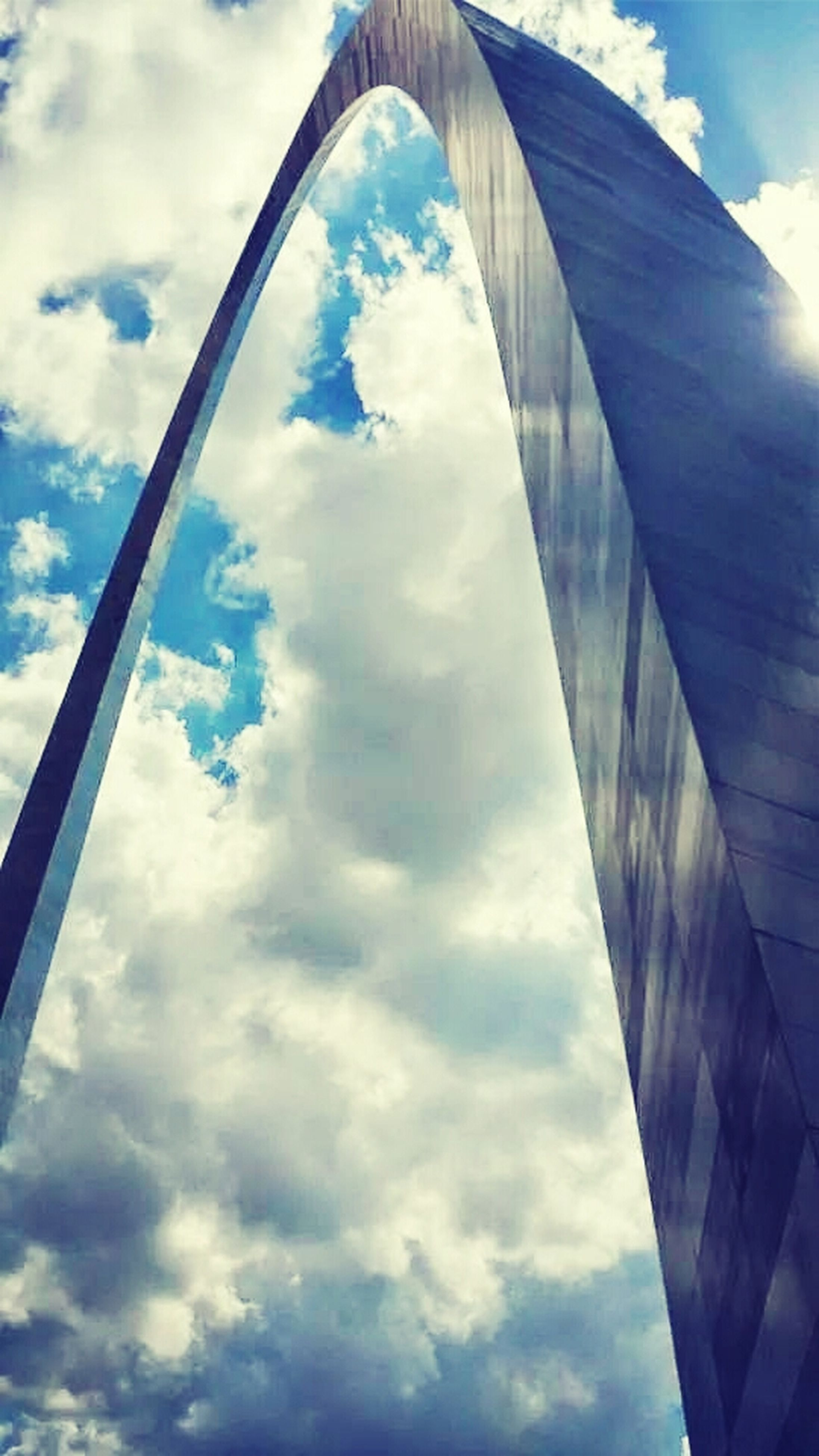sky, cloud - sky, low angle view, architecture, built structure, cloud, cloudy, reflection, modern, day, glass - material, blue, building exterior, city, outdoors, no people, directly below, sunlight, arch, part of