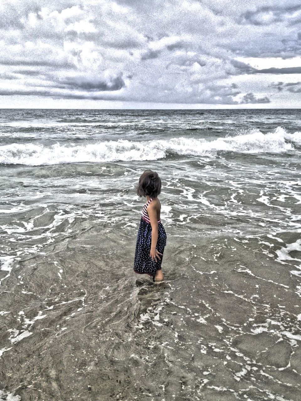 Girl Standing At Beach Against Cloudy Sky