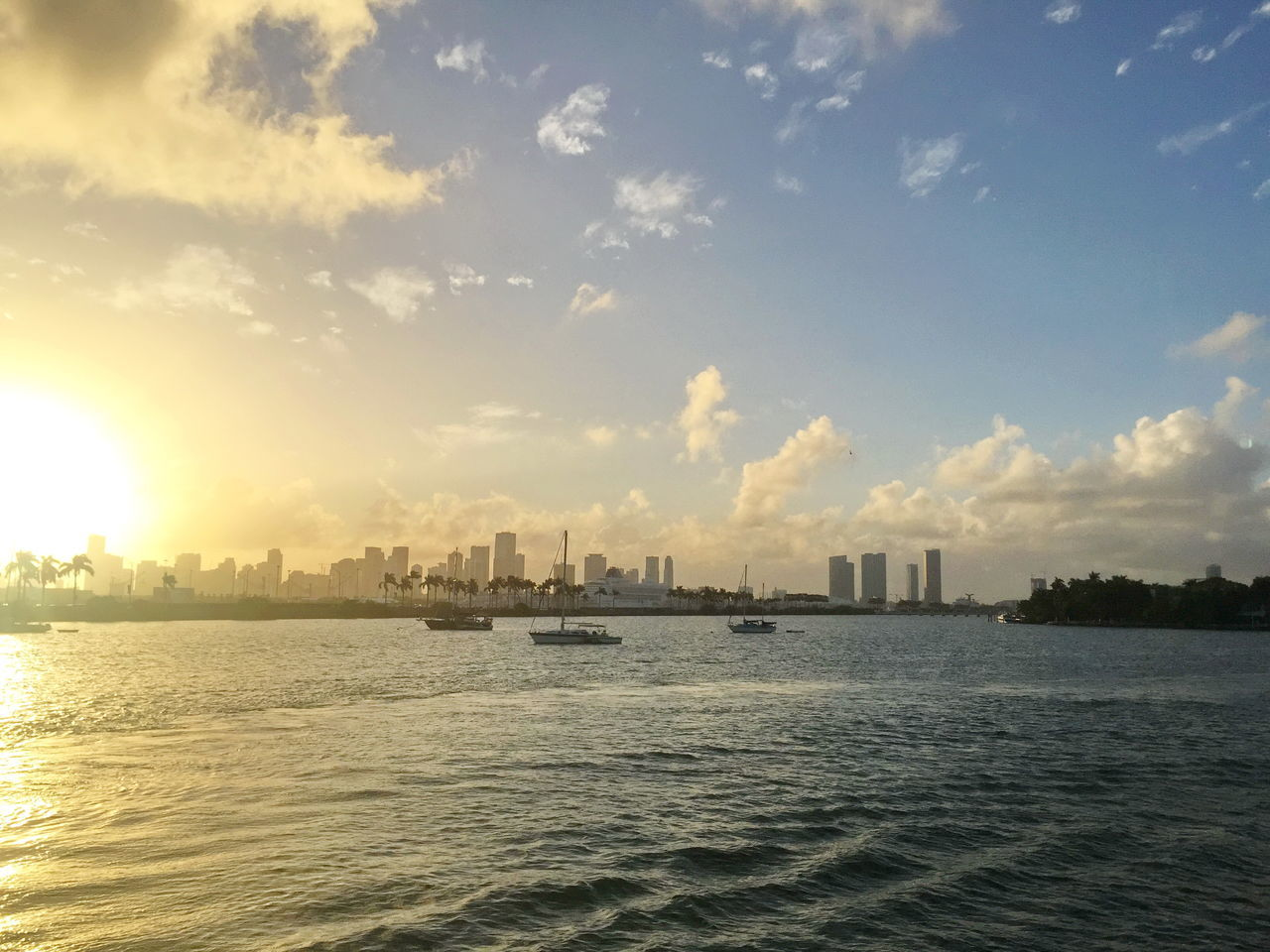 Skyscrapers In City By Sea Against Sky During Sunset