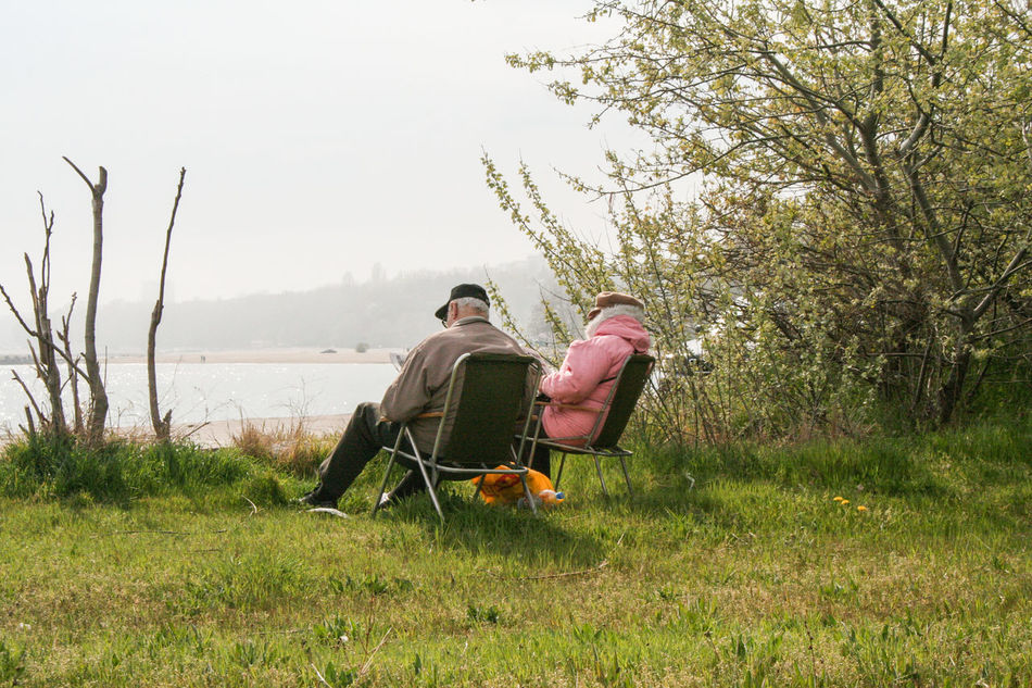 Adult Beauty In Nature Bonding Couple - Relationship Day Full Length Grass Leisure Activity Lifestyles Men Nature Outdoors People Relaxation Sitting Sky Togetherness Tranquil Scene Tranquility Tree Two People Vacations Water Young Adult