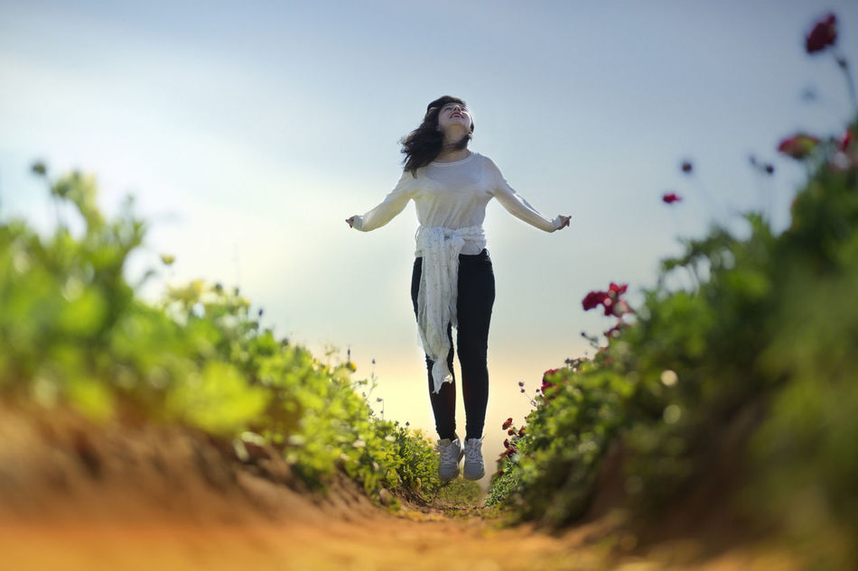 F L Y Beautiful Woman Casual Clothing Day Energetic Front View Full Length Jumping Leisure Activity Lifestyles Mid-air Nature One Person Outdoors People Plant Real People Sky Tree Young Adult Young Women