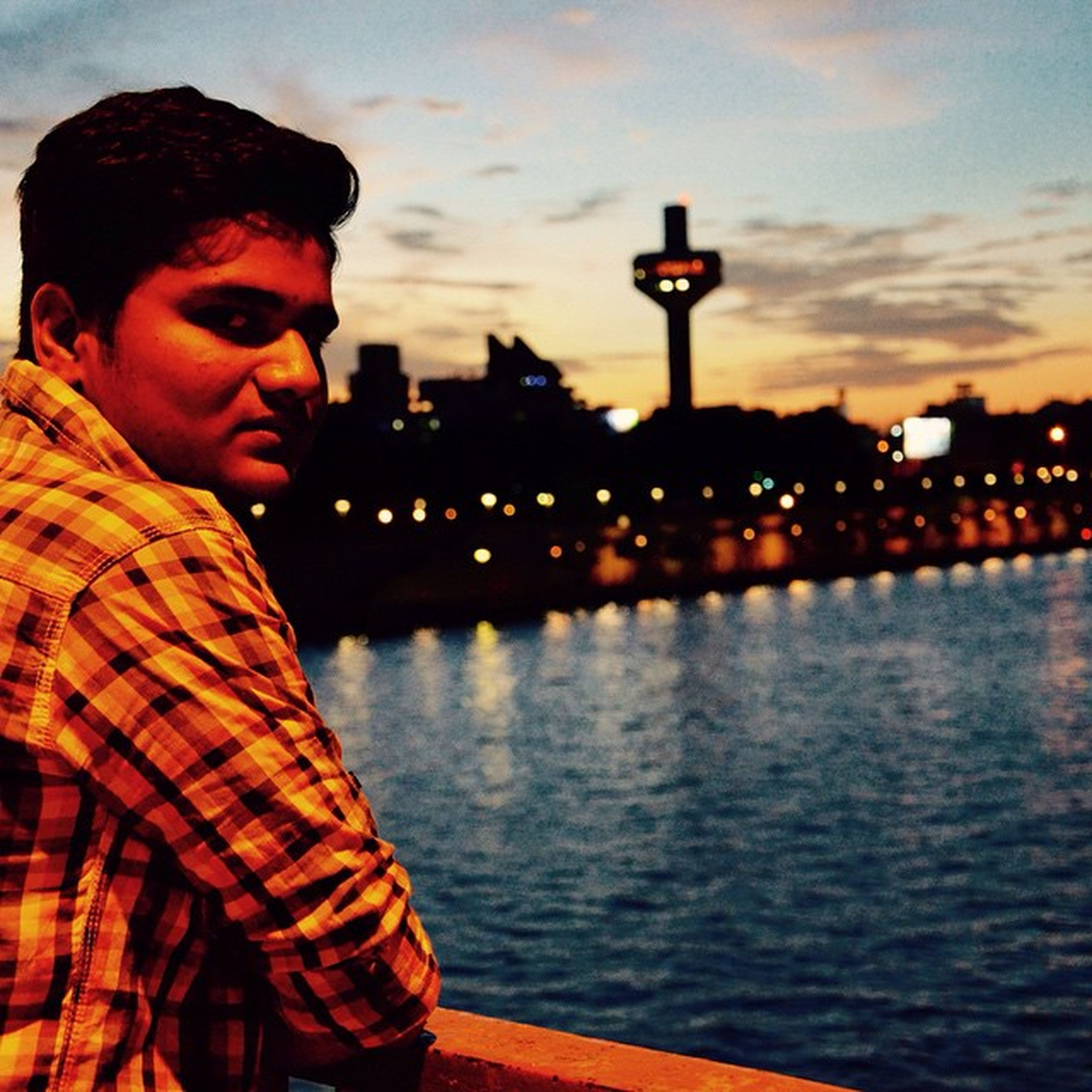 lifestyles, building exterior, water, architecture, person, built structure, leisure activity, headshot, young adult, river, sky, standing, city, looking at camera, casual clothing, waist up, portrait, young men