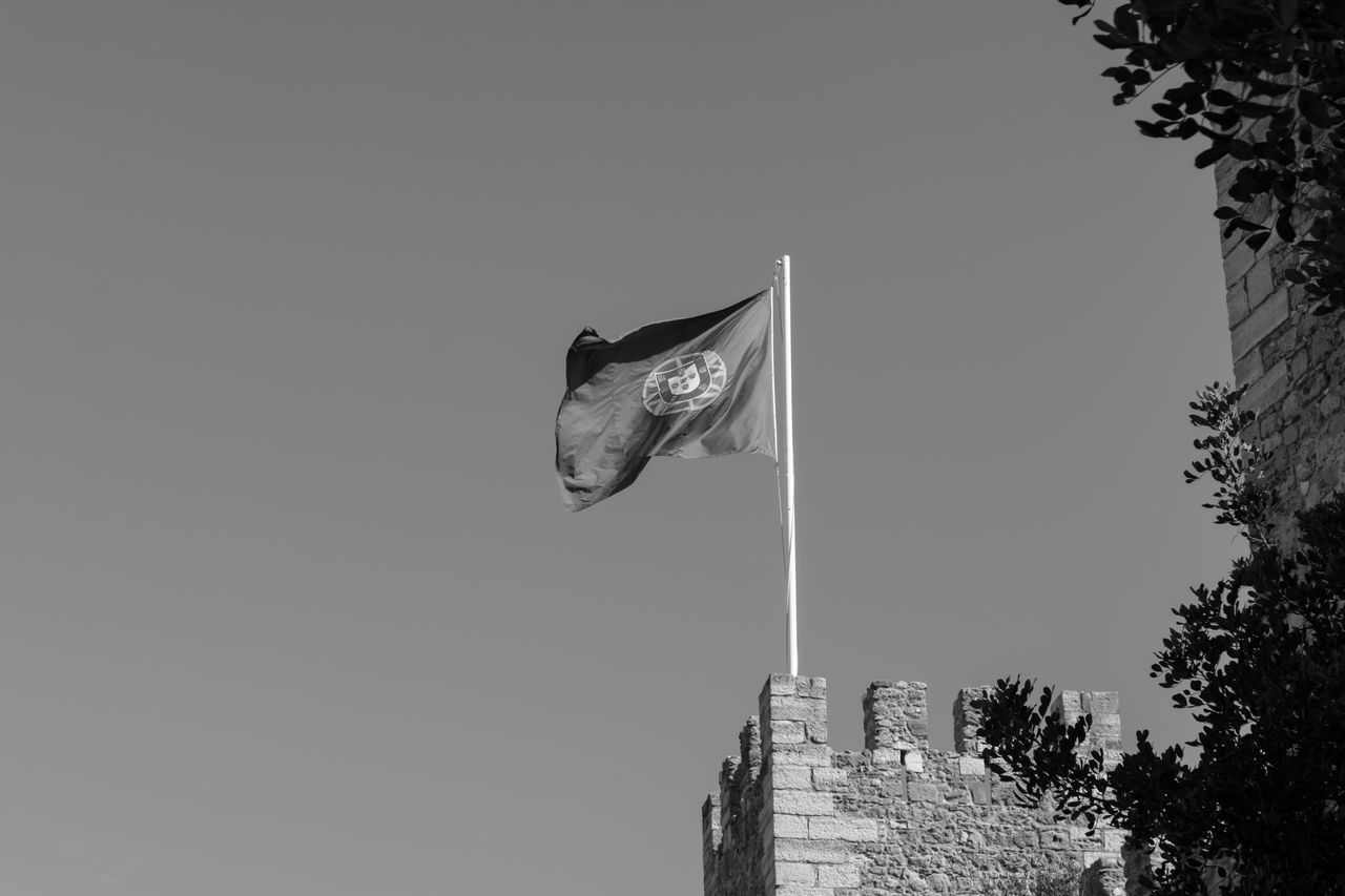 Portuguese Flag On Castelo Sao Jorge Against Clear Sky