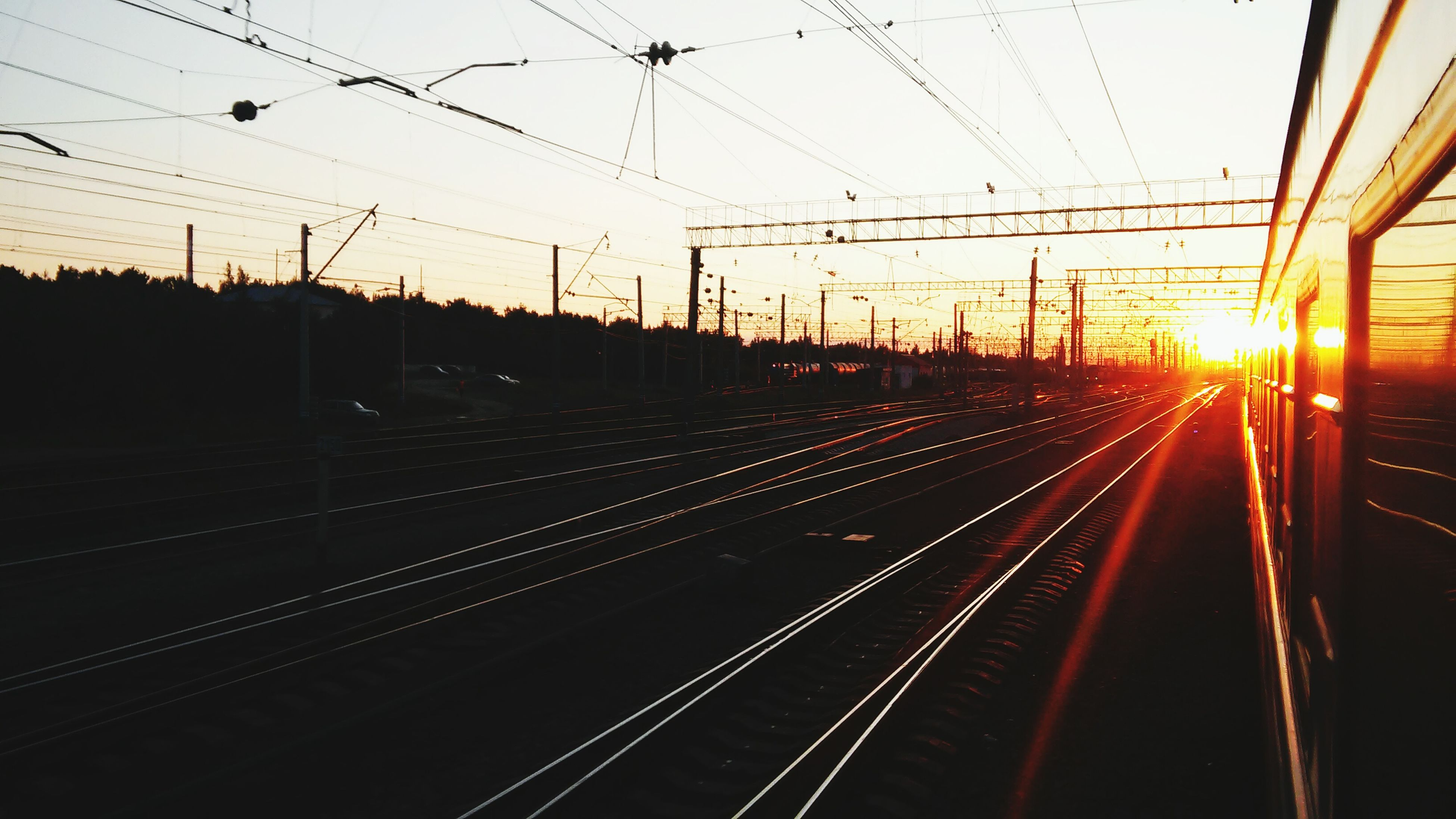 railroad track, rail transportation, transportation, public transportation, power line, sunset, electricity pylon, railroad station platform, railroad station, electricity, power supply, cable, train - vehicle, railway track, mode of transport, travel, sky, diminishing perspective, the way forward, train