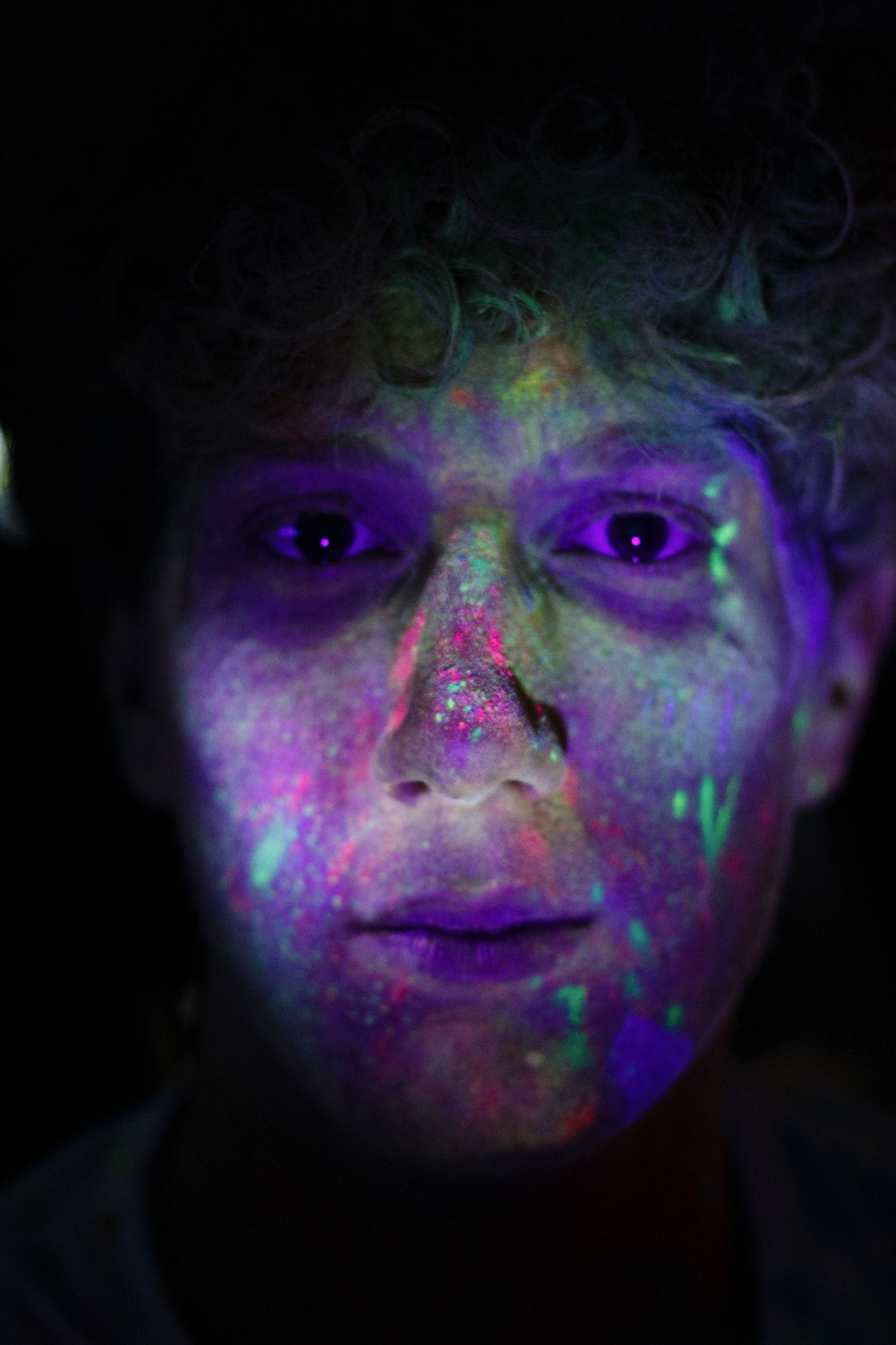 real people, multi colored, one person, headshot, portrait, black background, face paint, holi, men, close-up, young adult, outdoors, day, adult, people