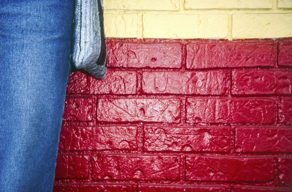 Woman, Blue Jeans, Painted Wall. USA Against The Wall Blue Blue Jean Blue Jeans Brick Brick Wall Bricks Casual Clothing Colour Colourful Day Graphic My Style One Person Outdoors Painted Bricks Painted Wall Red Urban USA Yellow