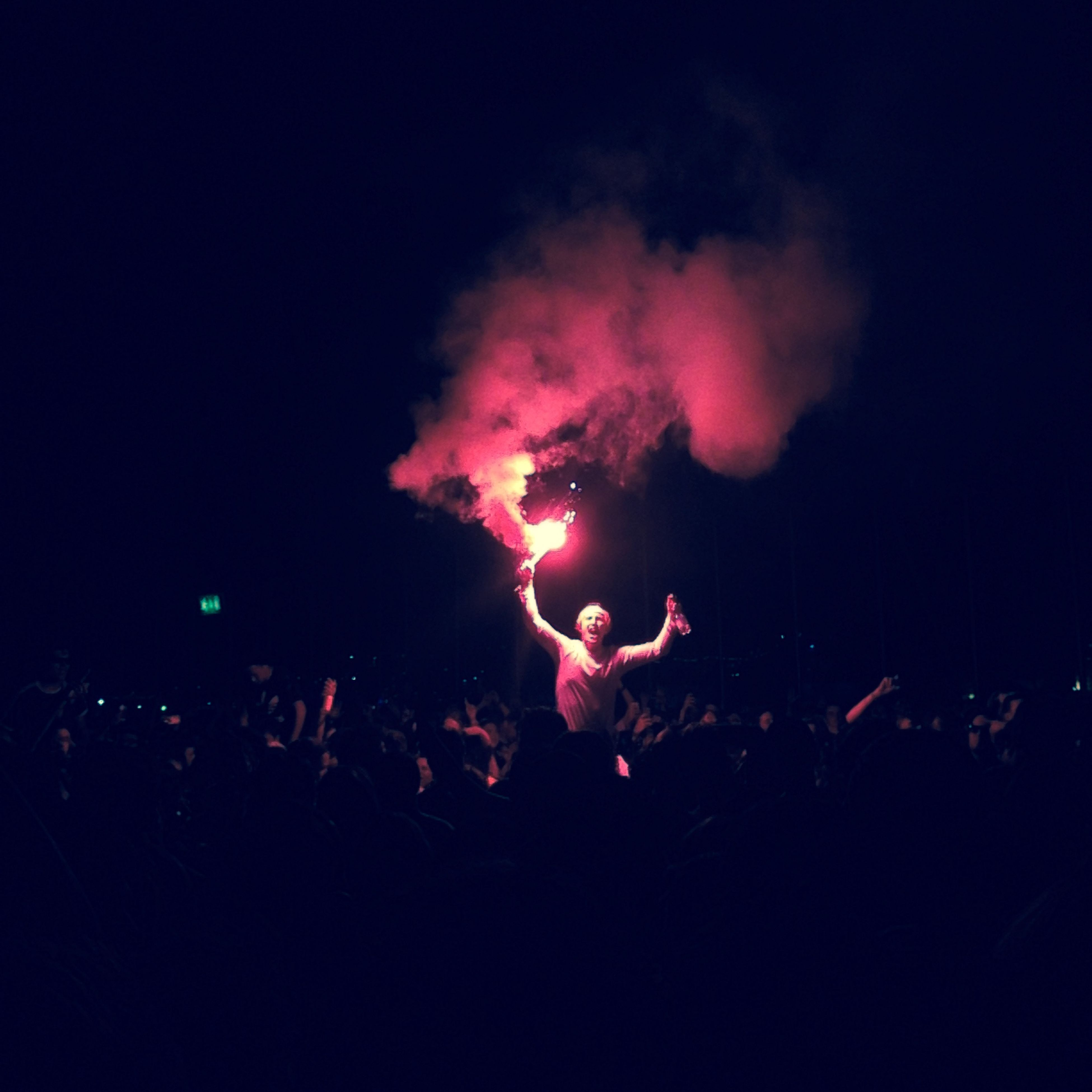 night, sky, silhouette, illuminated, large group of people, arts culture and entertainment, event, low angle view, celebration, light - natural phenomenon, crowd, smoke - physical structure, fun, enjoyment, outdoors, glowing, cloud - sky, motion, performance, excitement
