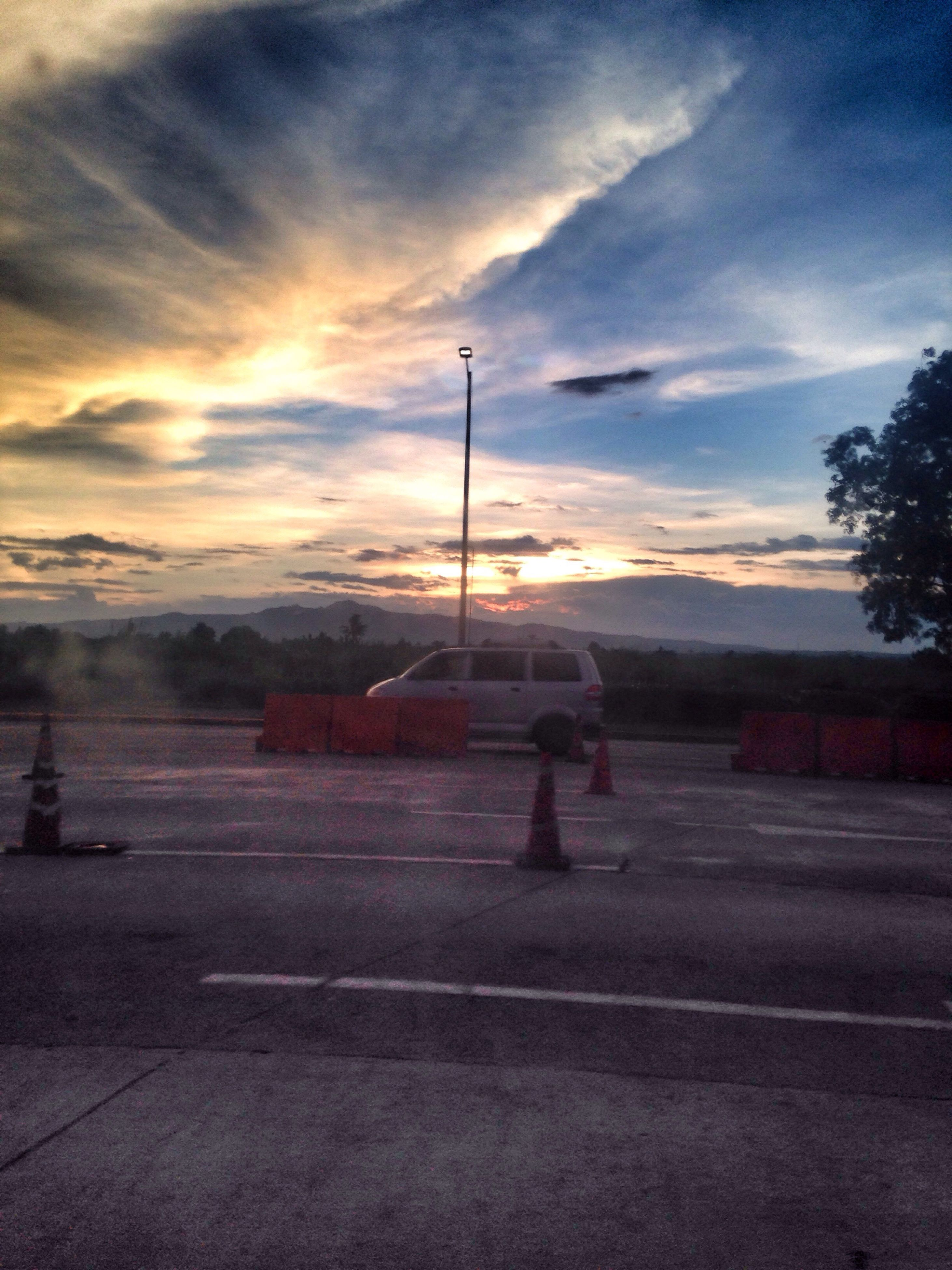 sunset, sky, road, cloud - sky, street light, the way forward, tree, orange color, cloud, landscape, tranquil scene, nature, tranquility, cloudy, scenics, country road, empty, outdoors, beauty in nature, dramatic sky, diminishing perspective, no people, illuminated, idyllic, vanishing point, weather, non-urban scene