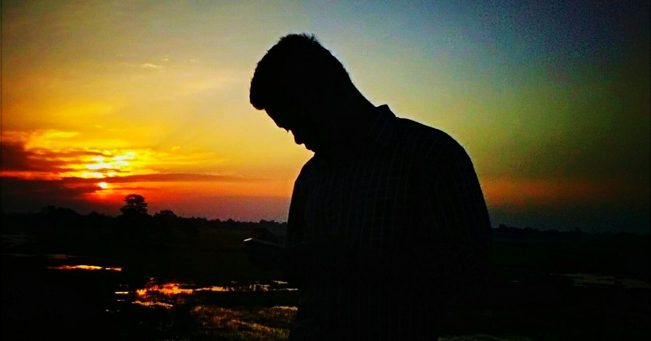 sunset, silhouette, orange color, sky, nature, one person, real people, beauty in nature, scenics, outdoors, side view, sun, men, cloud - sky, standing, landscape, lifestyles, tree, people